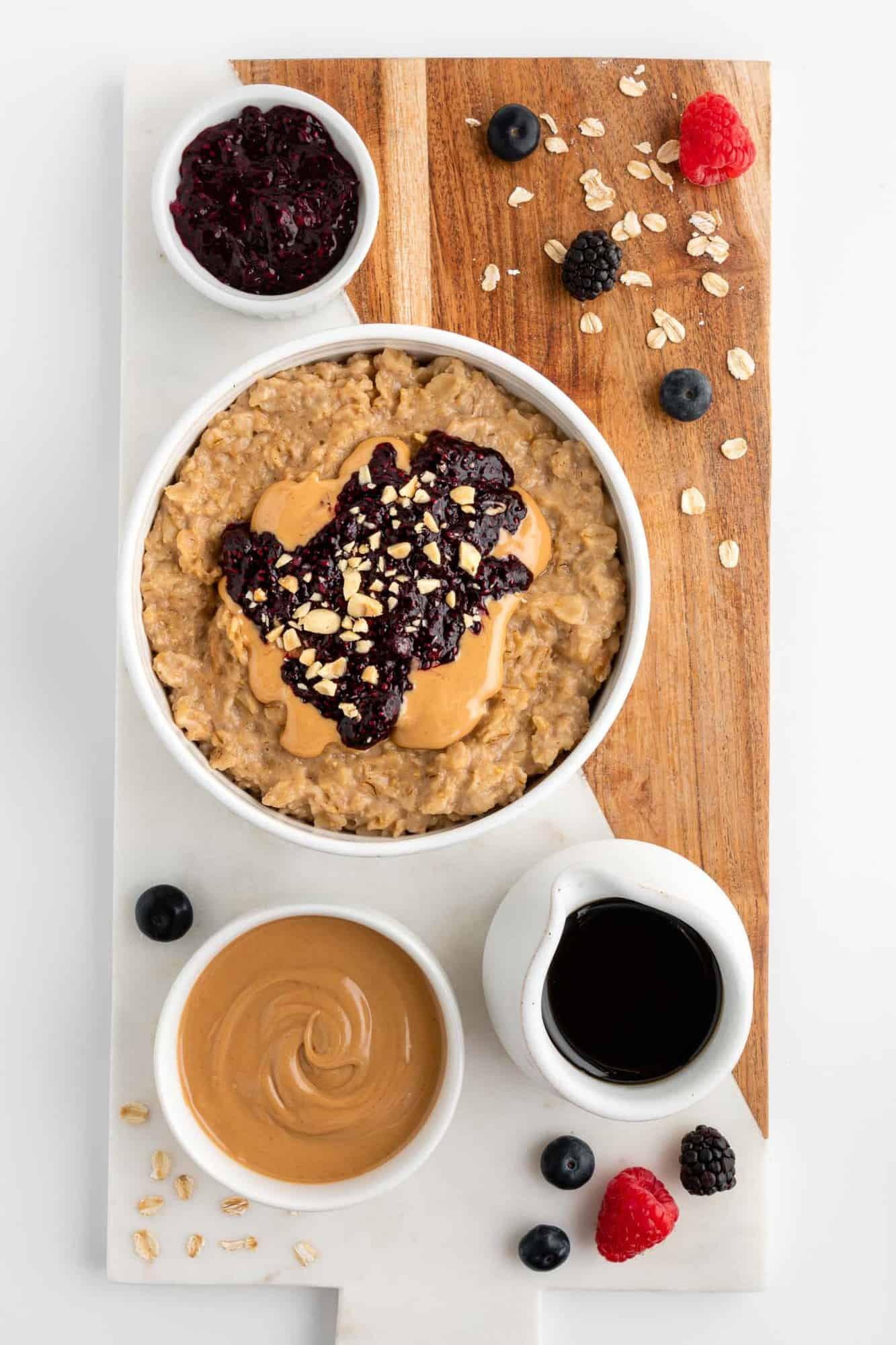 a wood and marble serving board topped with a bowl of pb&j oatmeal, a bowl of peanut butter, maple syrup, fresh berries, and oats