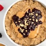 close up image of peanut butter and jelly oatmeal inside a white bowl