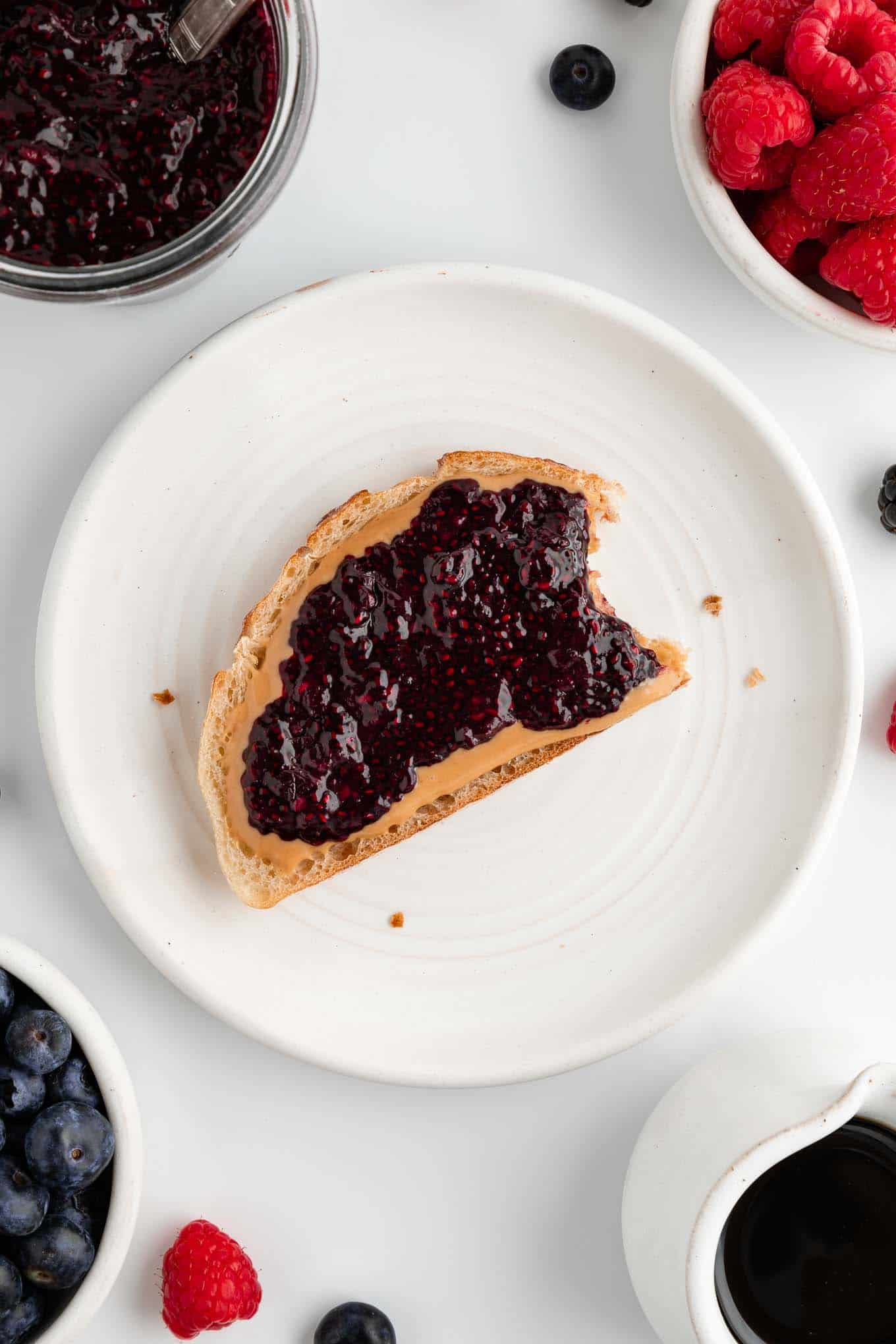 a partially eaten slice of peanut butter and berry chia jam toast on a white plate