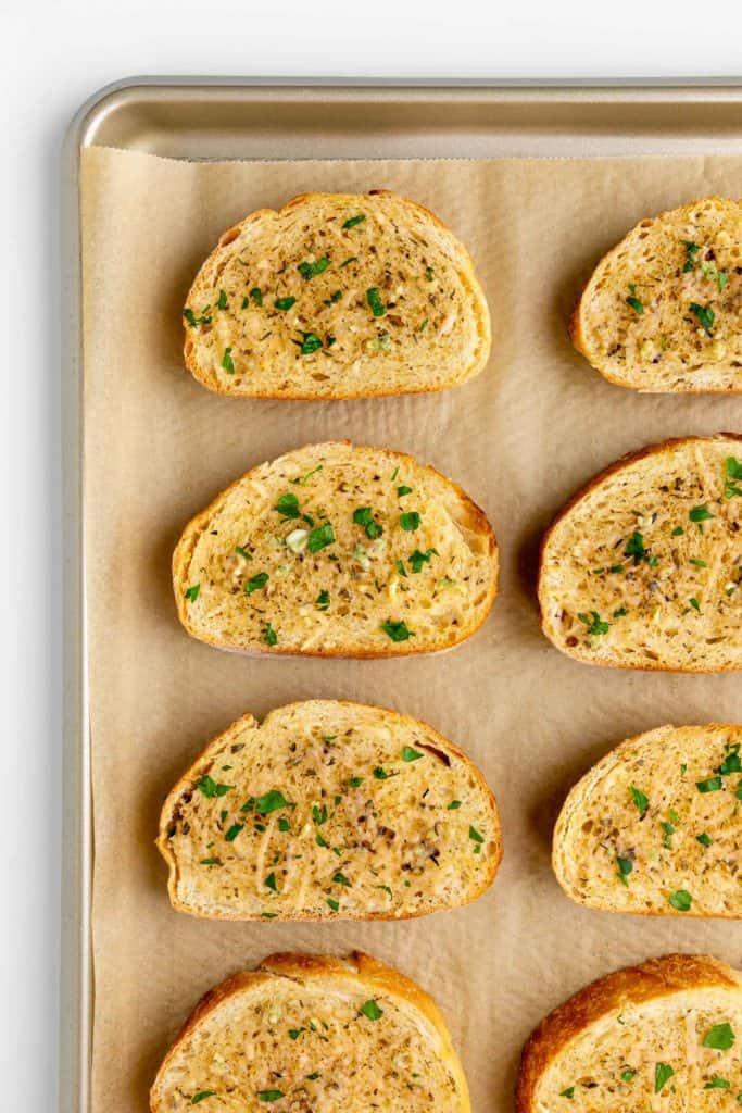slices of sourdough vegan garlic bread on a baking sheet