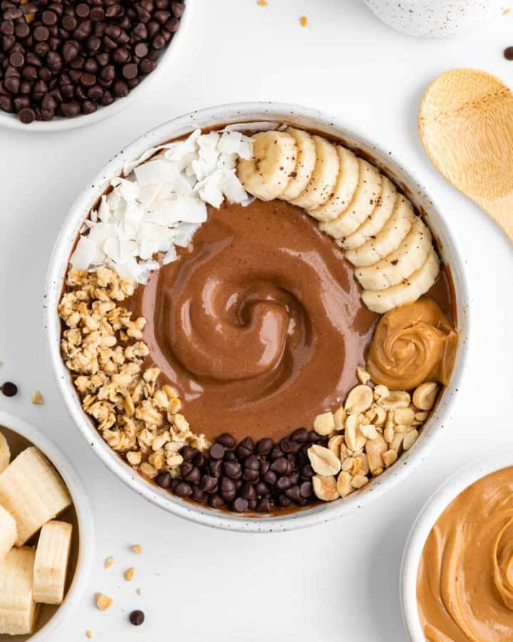 chocolate peanut butter smoothie bowl surrounded by bowls of ingredients, including banana, chocolate chips, and almond milk