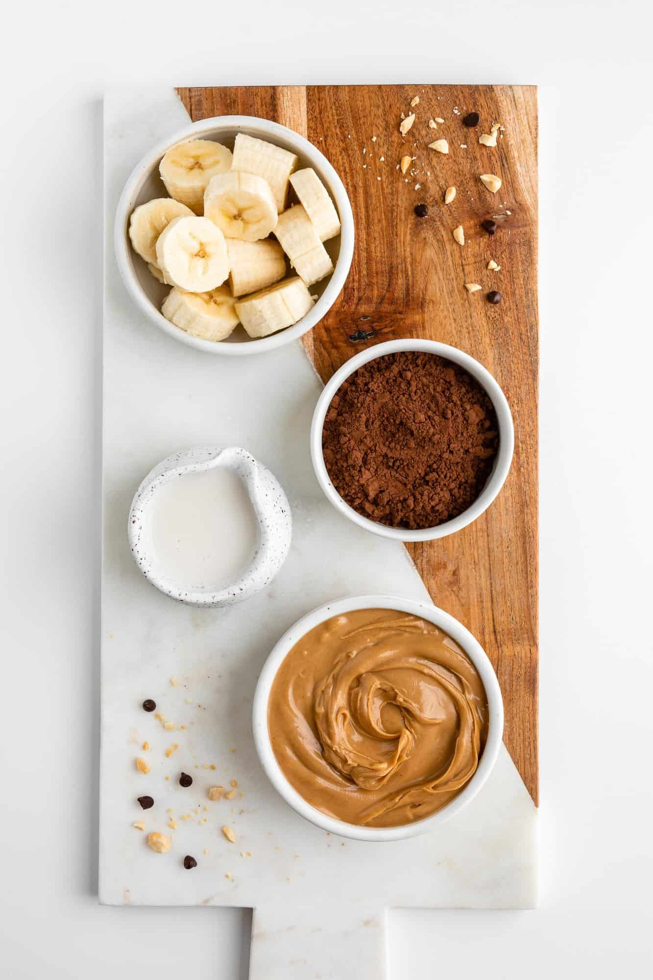 a wood and marble serving board topped with small bowls containing banana, cocoa powder, peanut butter, and almond milk