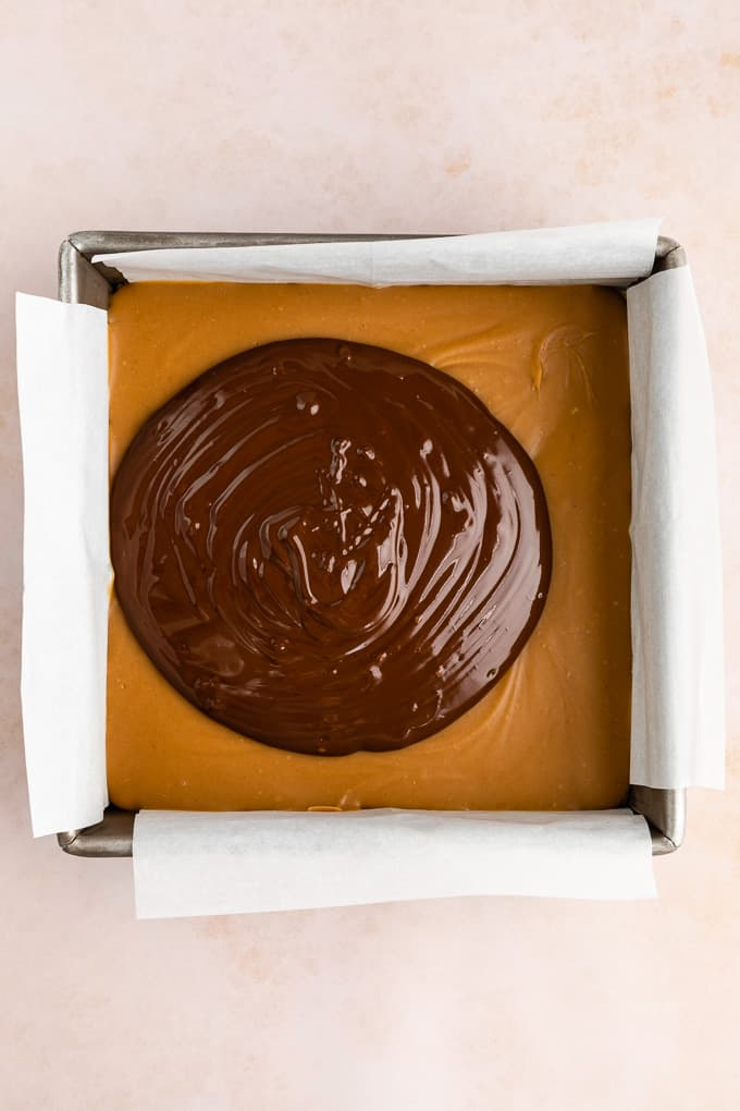 a puddle of melted chocolate on top of a chilled caramel layer in a square baking dish