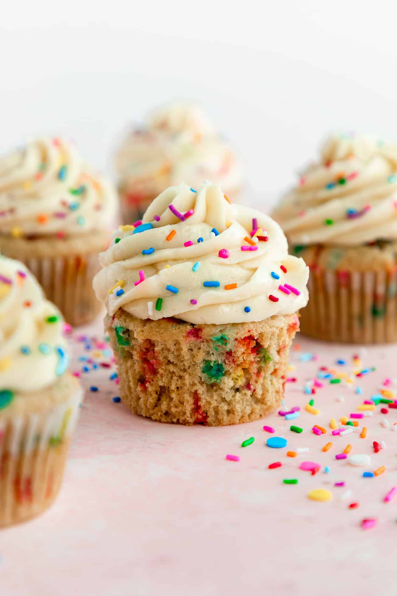 vegan funfetti cupcakes with vanilla frosting and rainbow sprinkles on a pink surface