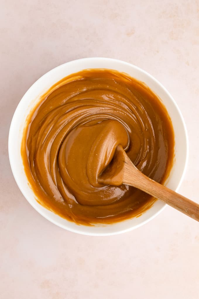 a wooden spoon mixing healthy vegan peanut butter caramel in a white bowl