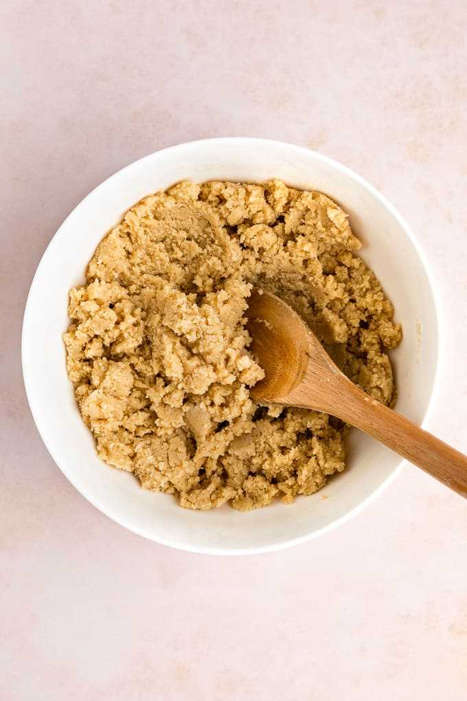 vegan shortbread cookie dough inside a white bowl with a wooden spoon
