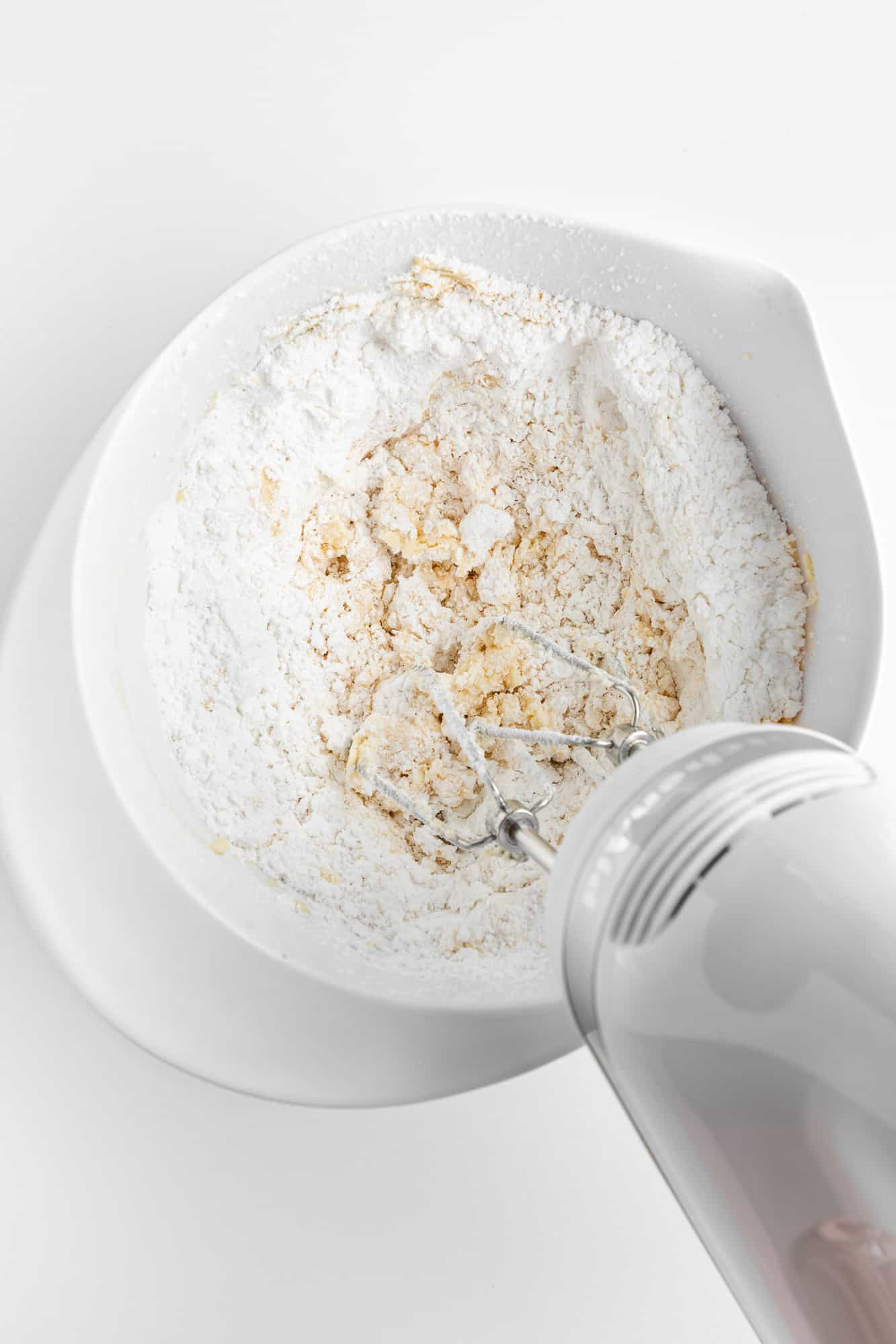 powdered sugar and vegan butter being mixed with a handheld electric mixer in a white bowl