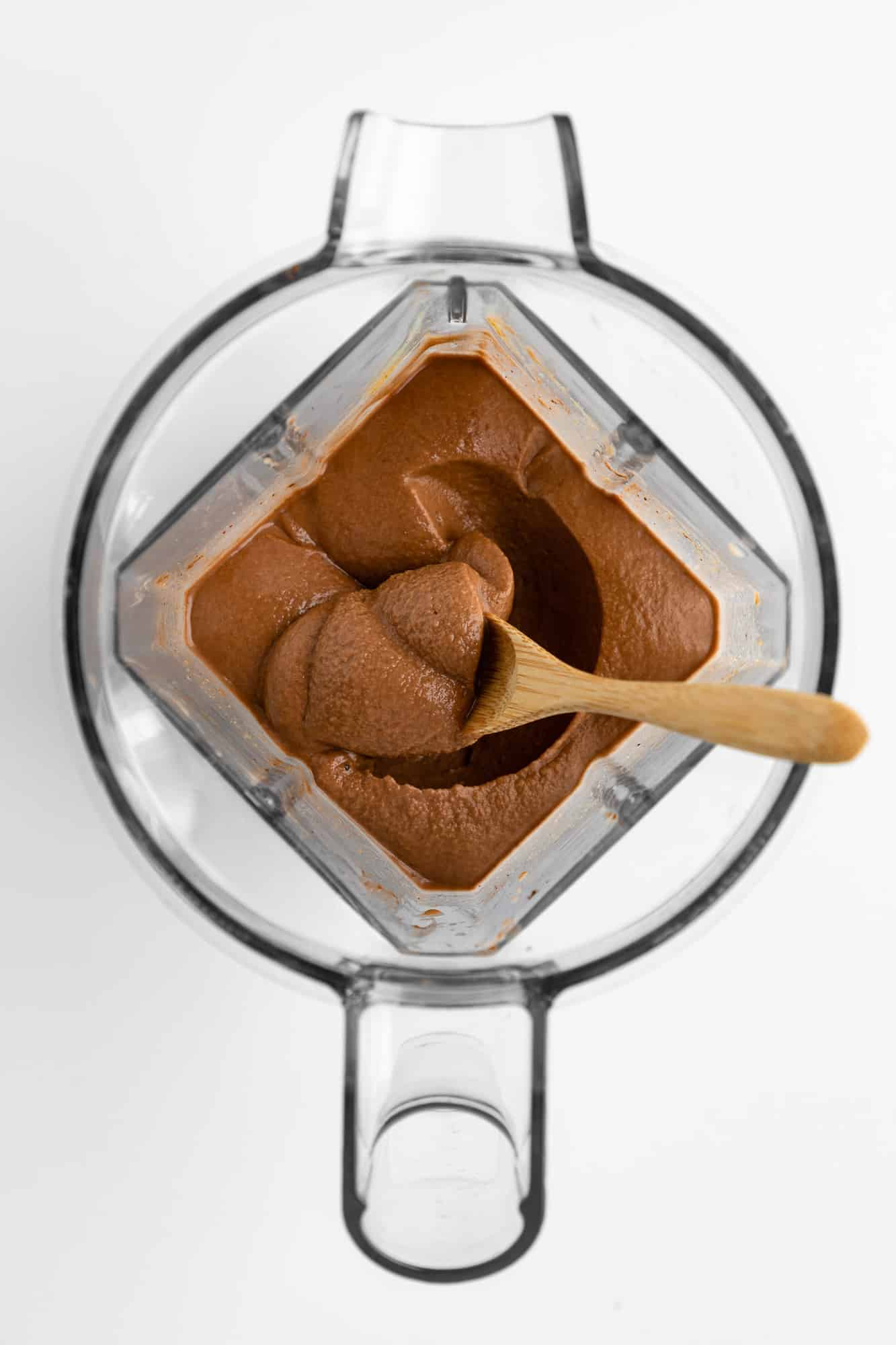 a wooden spoon scooping thick chocolate smoothie out of a vitamix blender