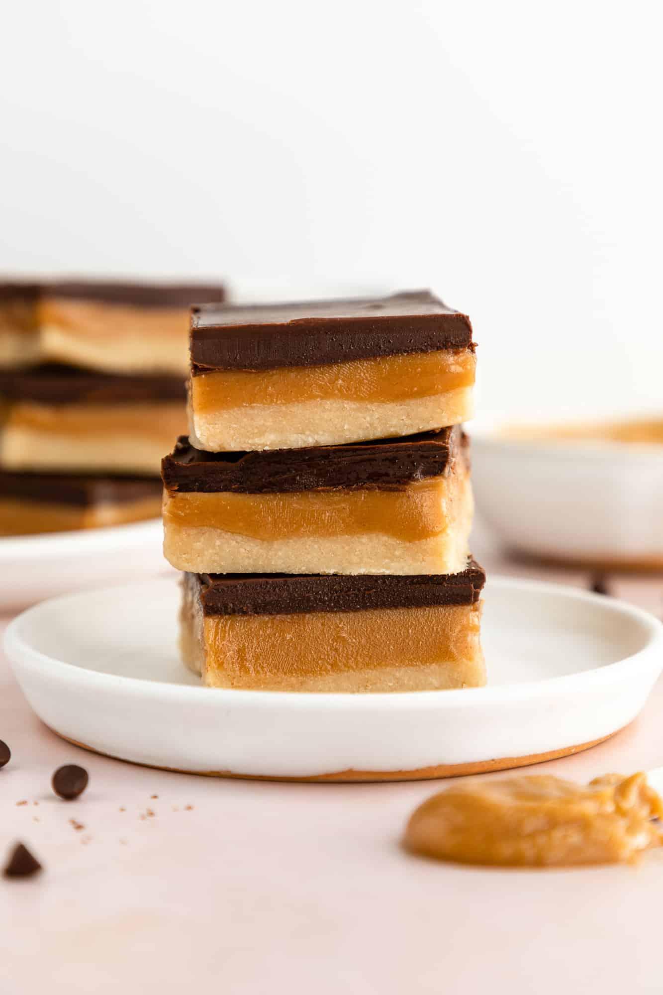 three no-bake vegan millionaire shortbread bars stacked on a white plate