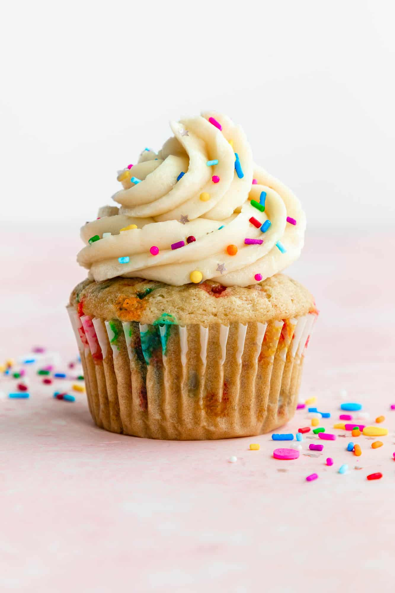 a vegan funfetti cupcake topped with vanilla buttercream frosting and rainbow sprinkles
