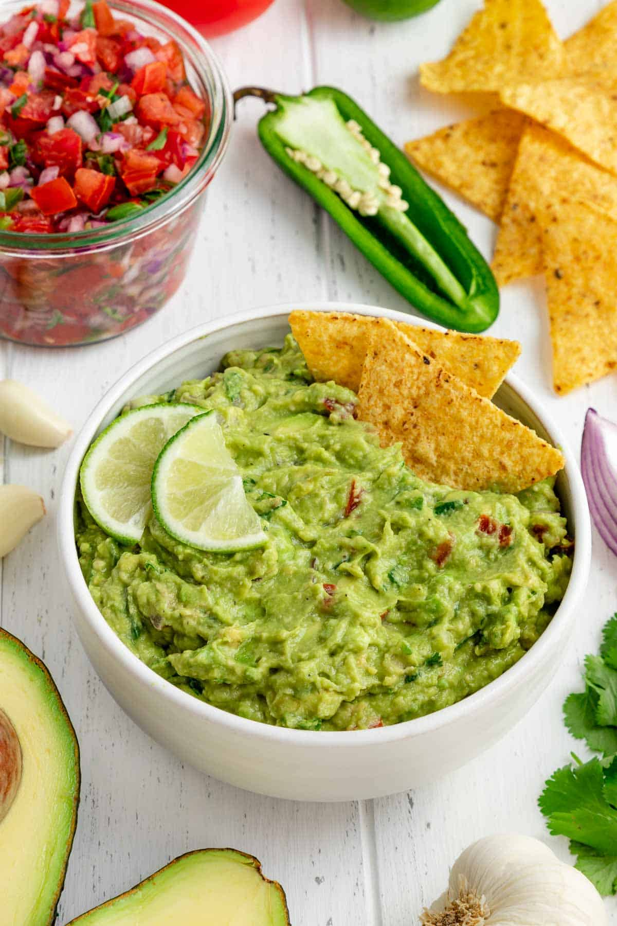 best guacamole in a white bowl with corn tortilla chips, limes, and surrounded by guac ingredients