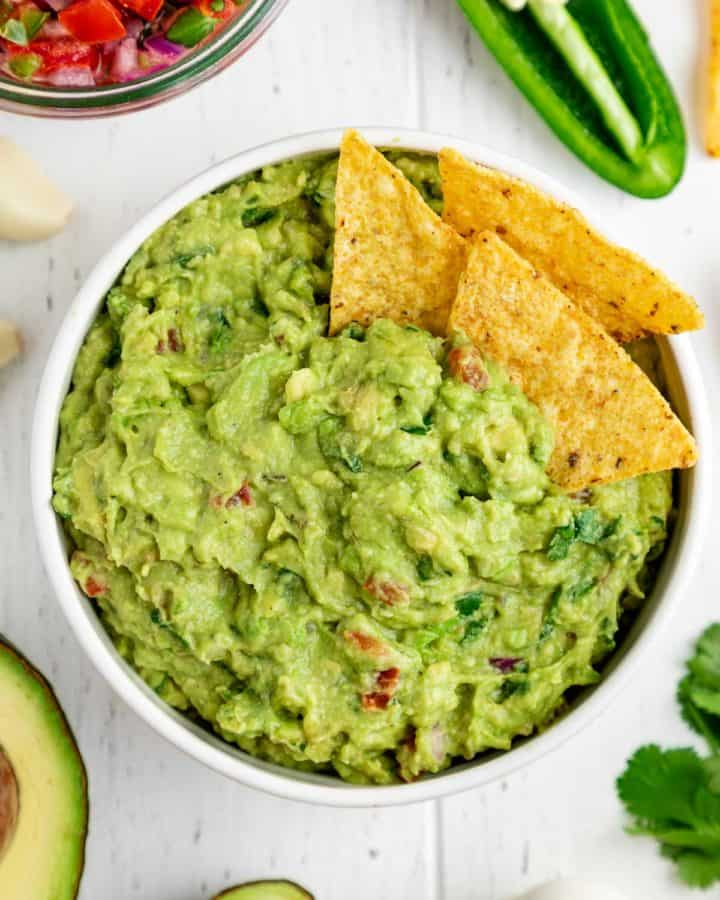 corn tortilla chips inside a bowl of guacamole surrounded by guac ingredients