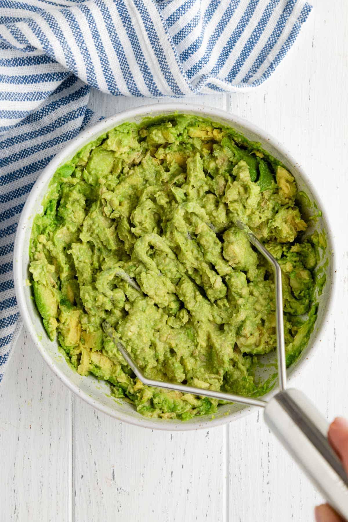mashing avocado in a bowl