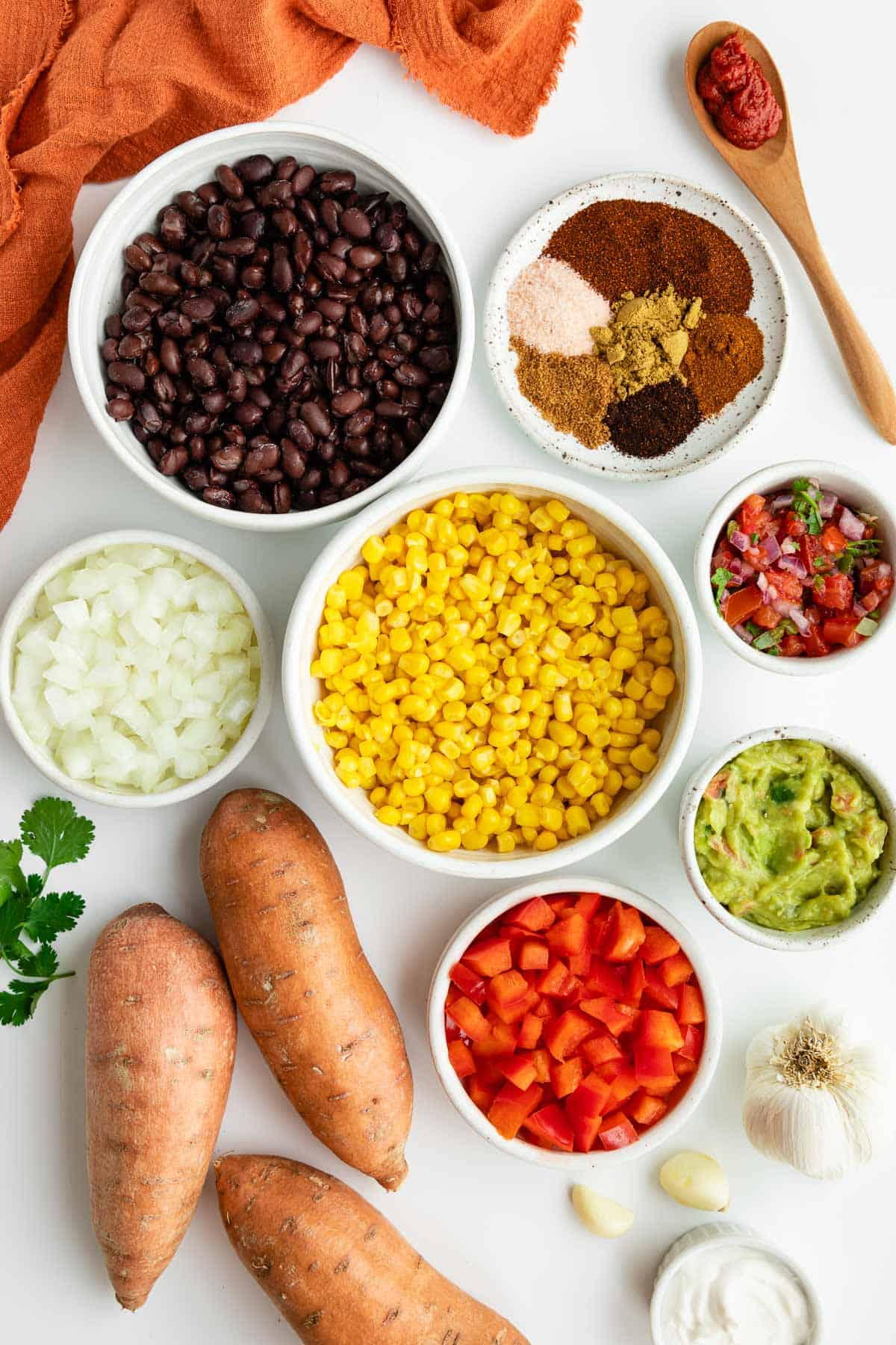 bowls of black beans, corn, onion, red peppers, spices, guacamole, pico de gallo, and three sweet potatoes