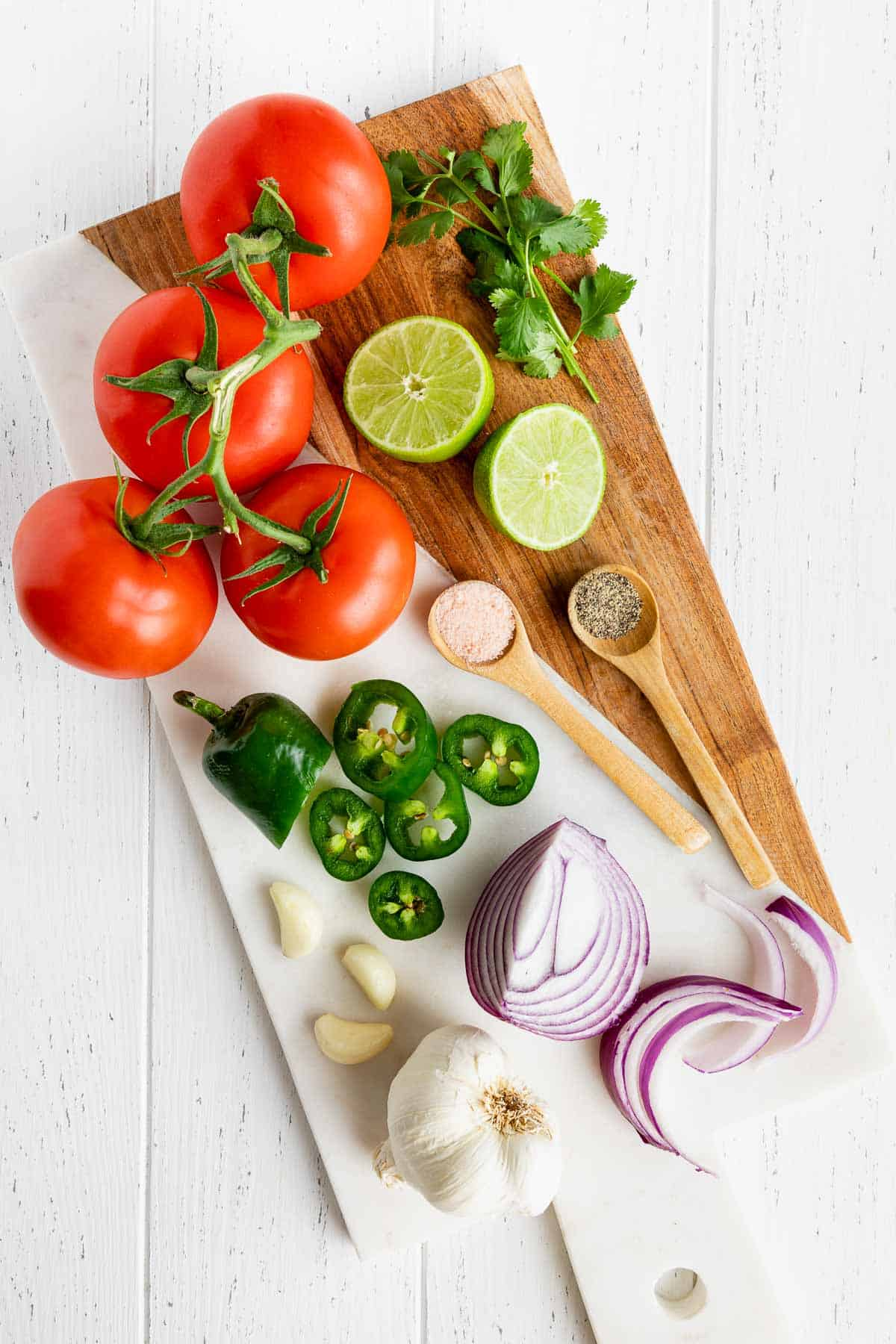 tomatoes, limes, red onion, cilantro, garlic, and jalapeño on a wood and marble serving board