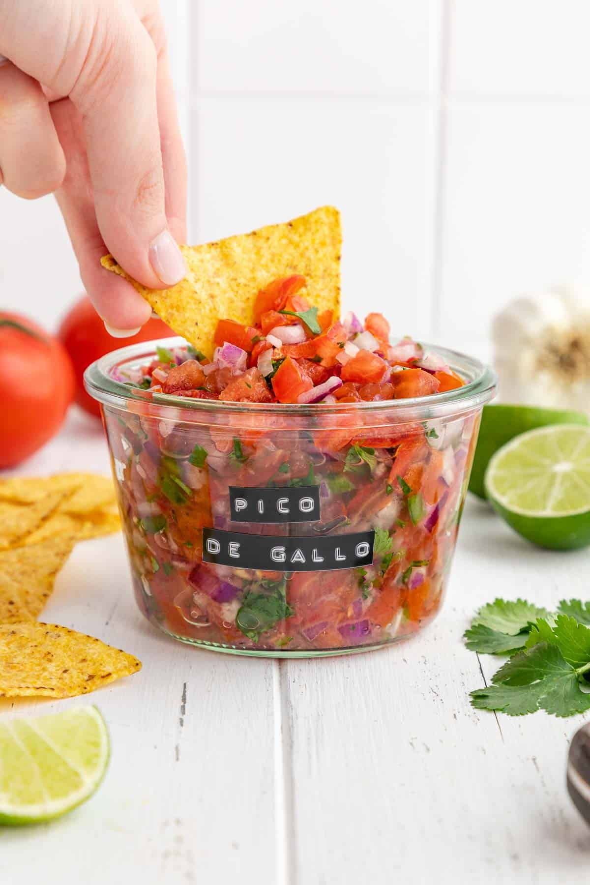 tortilla chip scooping pico de gallo from a weck jar