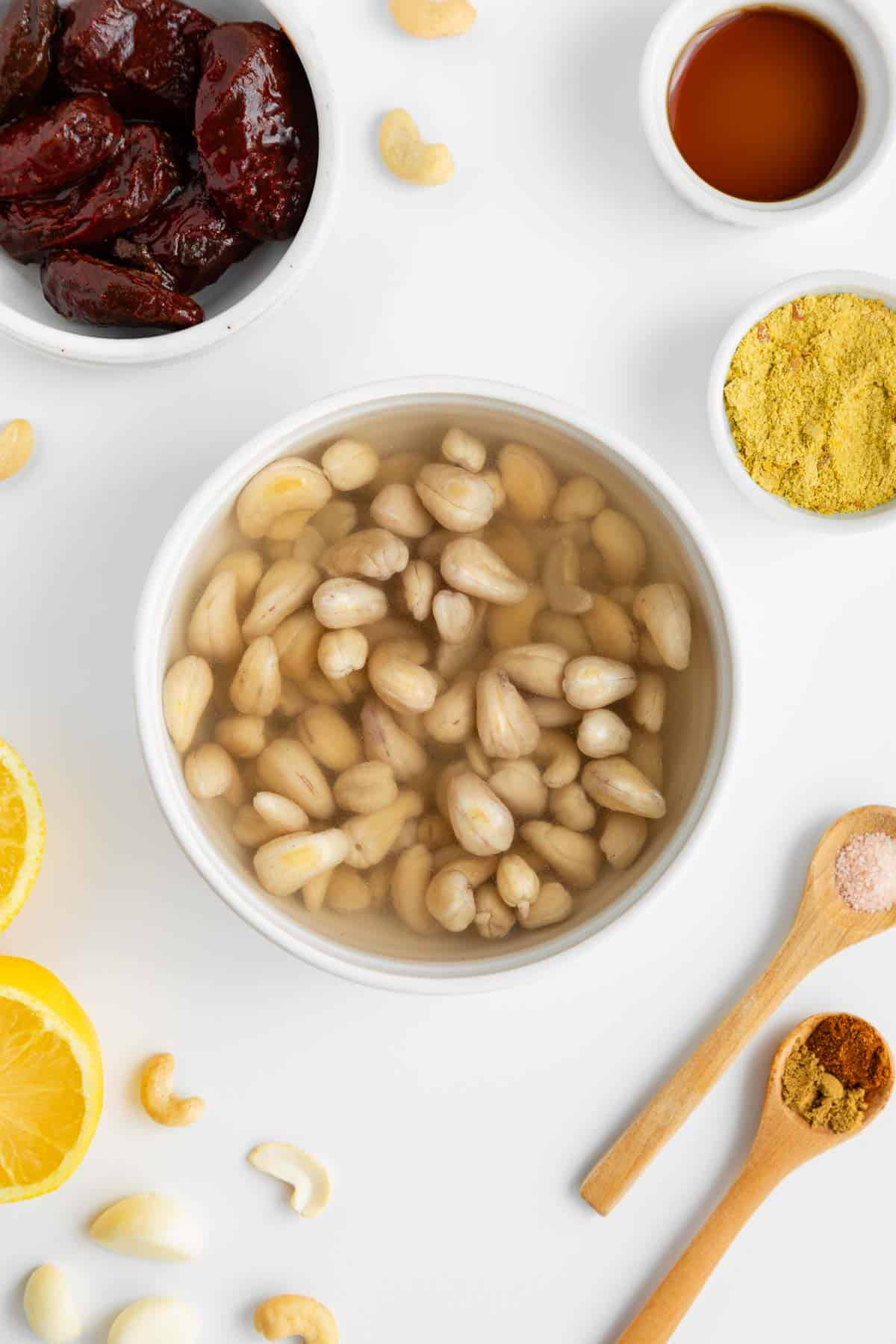 raw cashews soaking in water inside a white bowl surrounded by ingredients for vegan chipotle aioli