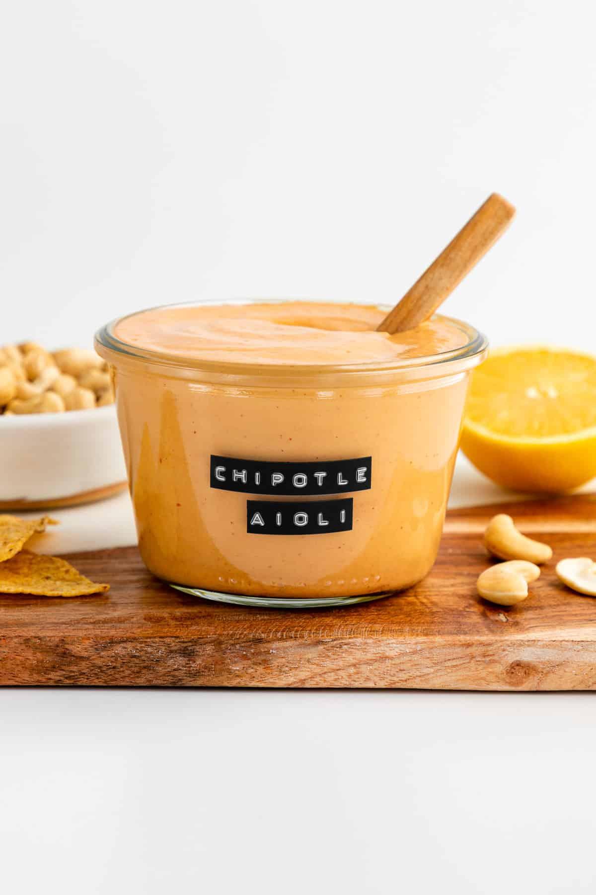 vegan chipotle sauce in a glass weck jar beside cashews and lemon