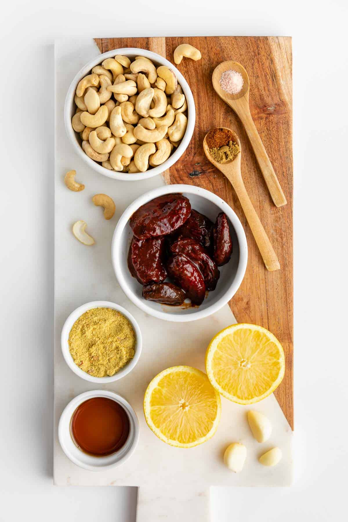 cashews, chipotle peppers in adobo sauce, lemon, nutritional yeast, maple syrup, and spices on a marble serving board