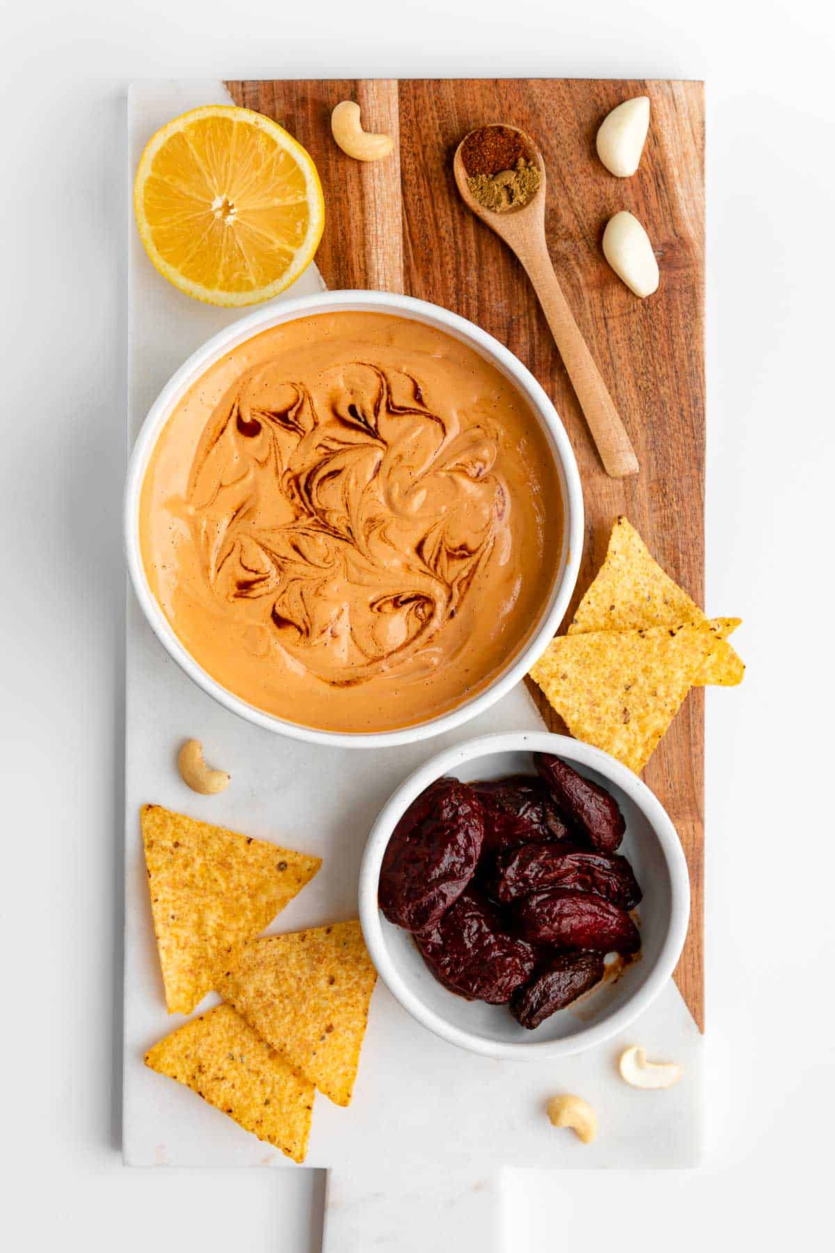 a marble serving board with a bowl of vegan chipotle aioli, tortilla chips, peppers in adobo sauce, lemon, and cashews on top