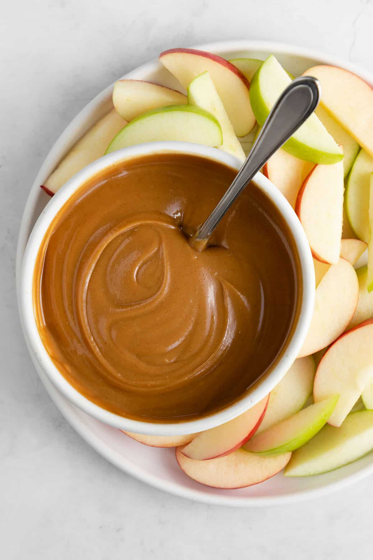 healthy caramel dip in a white bowl with a spoon surrounded by apple slices
