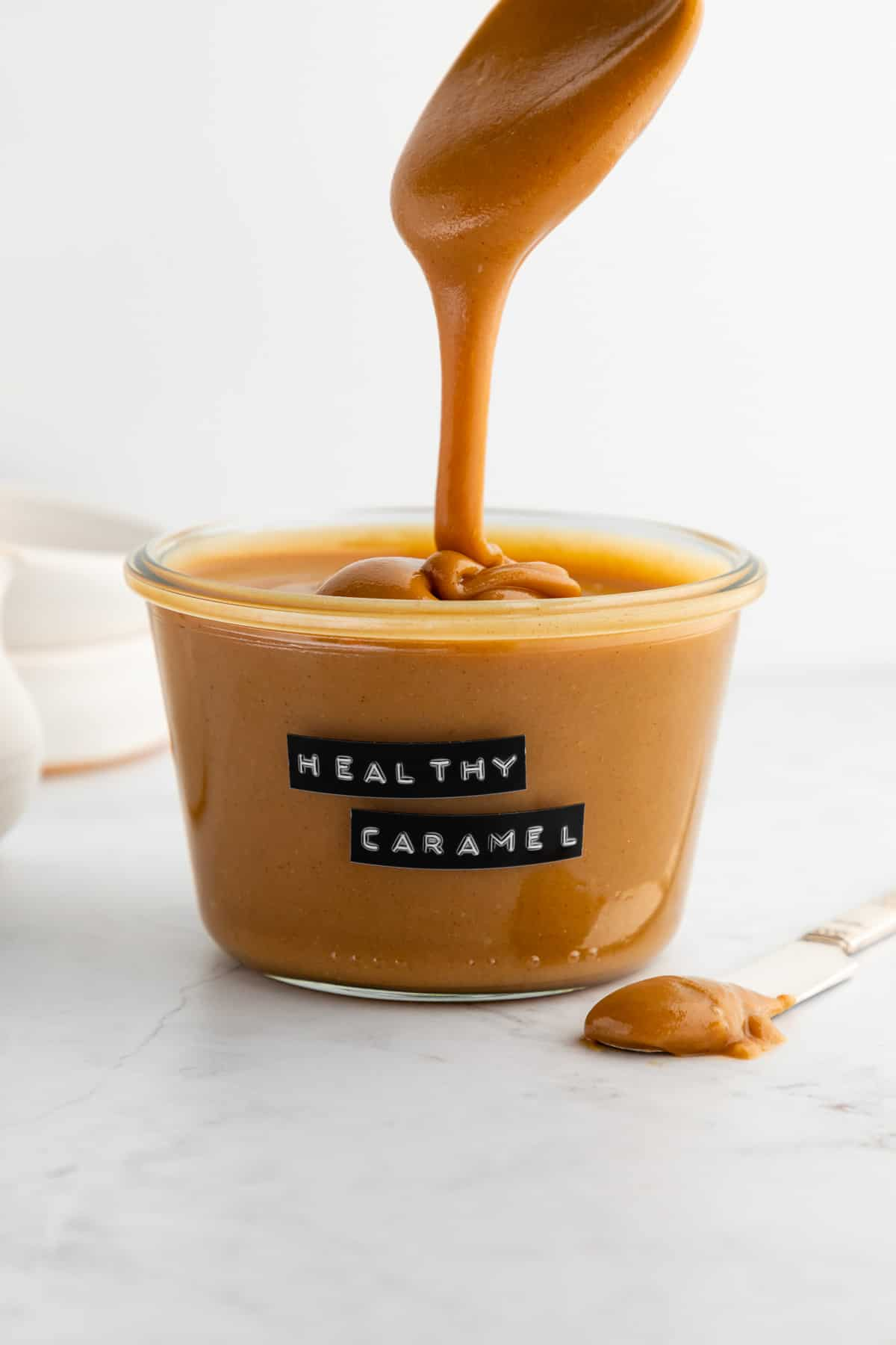 a spoon drizzling vegan peanut butter caramel sauce into a glass weck jar
