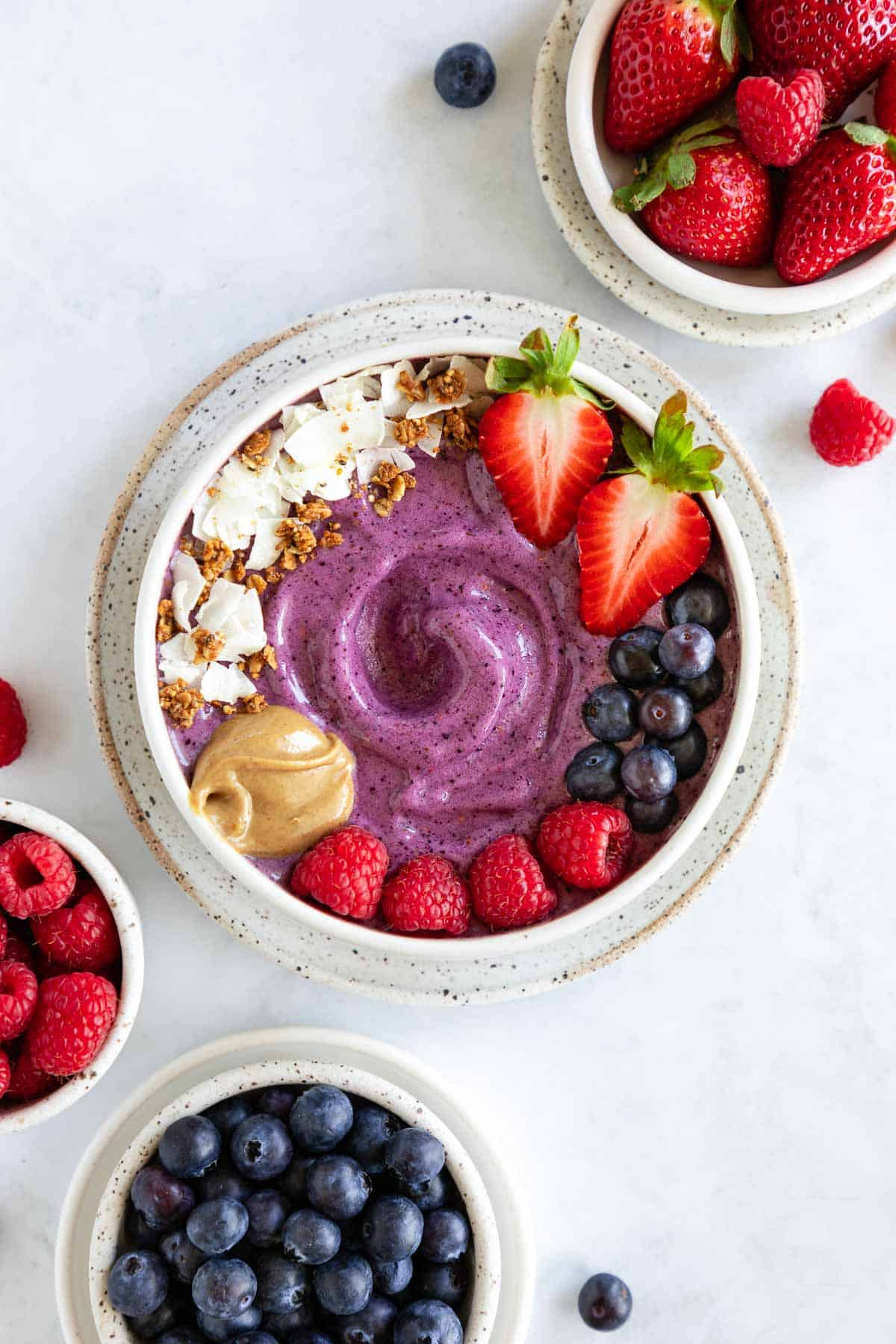 berry smoothie bowl on a speckled ceramic plate surrounded by bowls of blueberries, raspberries, and strawberries