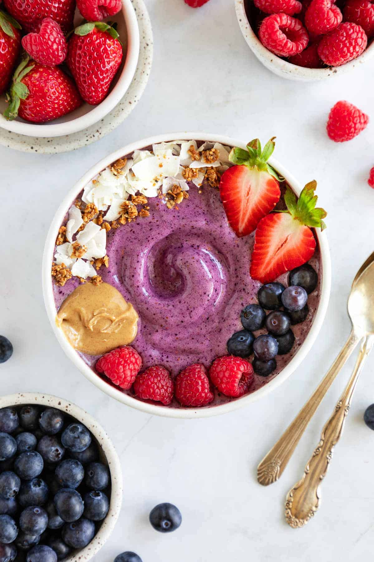 a berry smoothie bowl surrounded by bowls of strawberries, raspberries, and blueberries