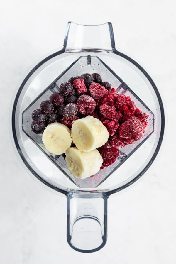 frozen blueberries, frozen raspberries, and frozen bananas in a vitamix blender