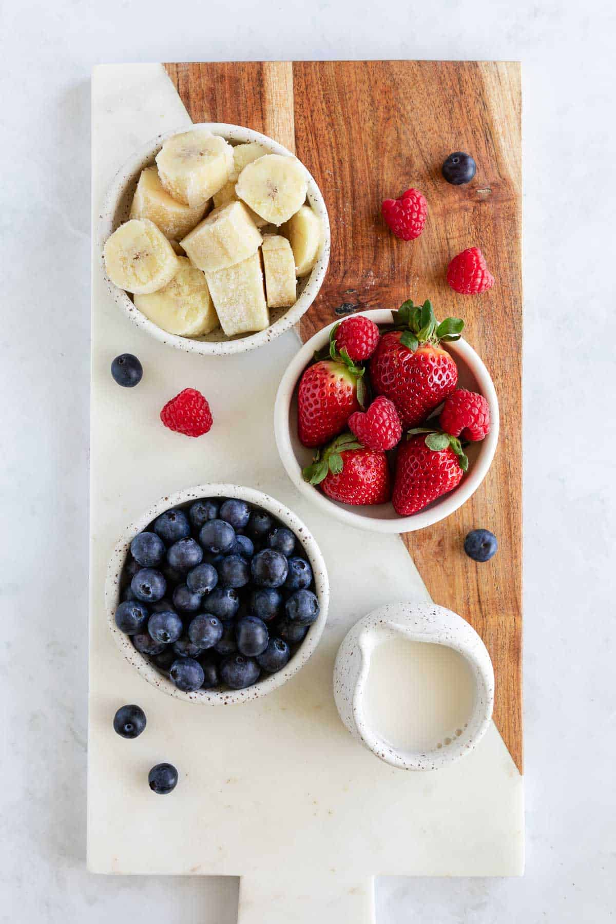 a marble and wood serving board topped with small ceramic bowls filled with frozen bananas, strawberries, blueberries, and almond milk