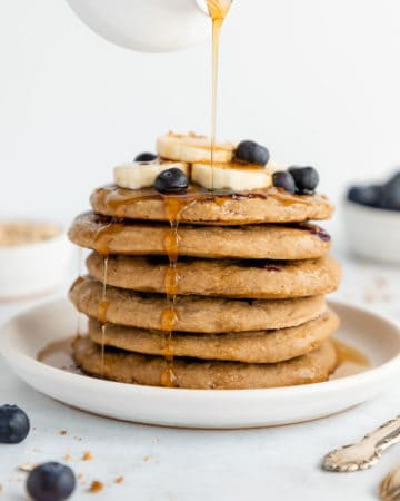 maple syrup being poured over a stack of vegan gluten-free blueberry banana pancakes