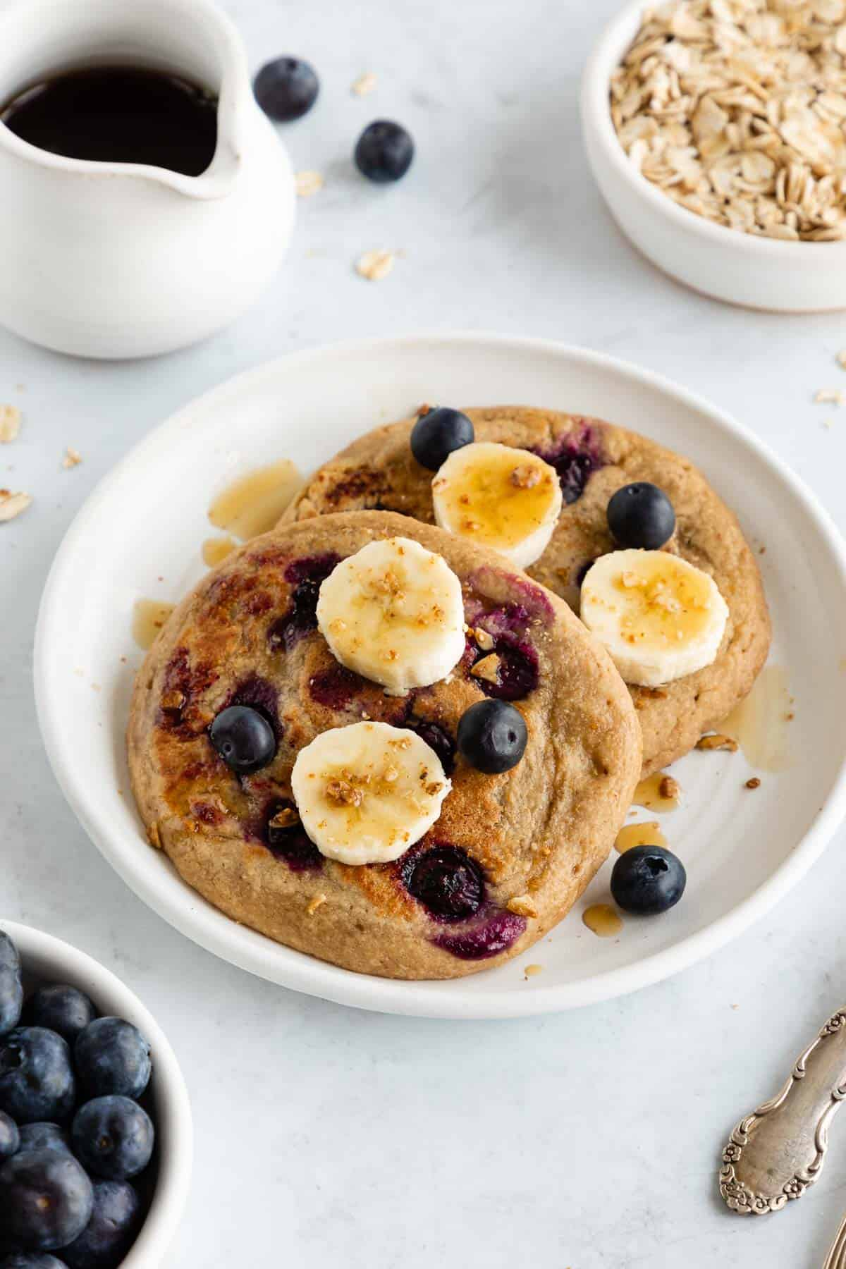 two vegan blueberry banana pancakes on a white plate topped with maple syrup