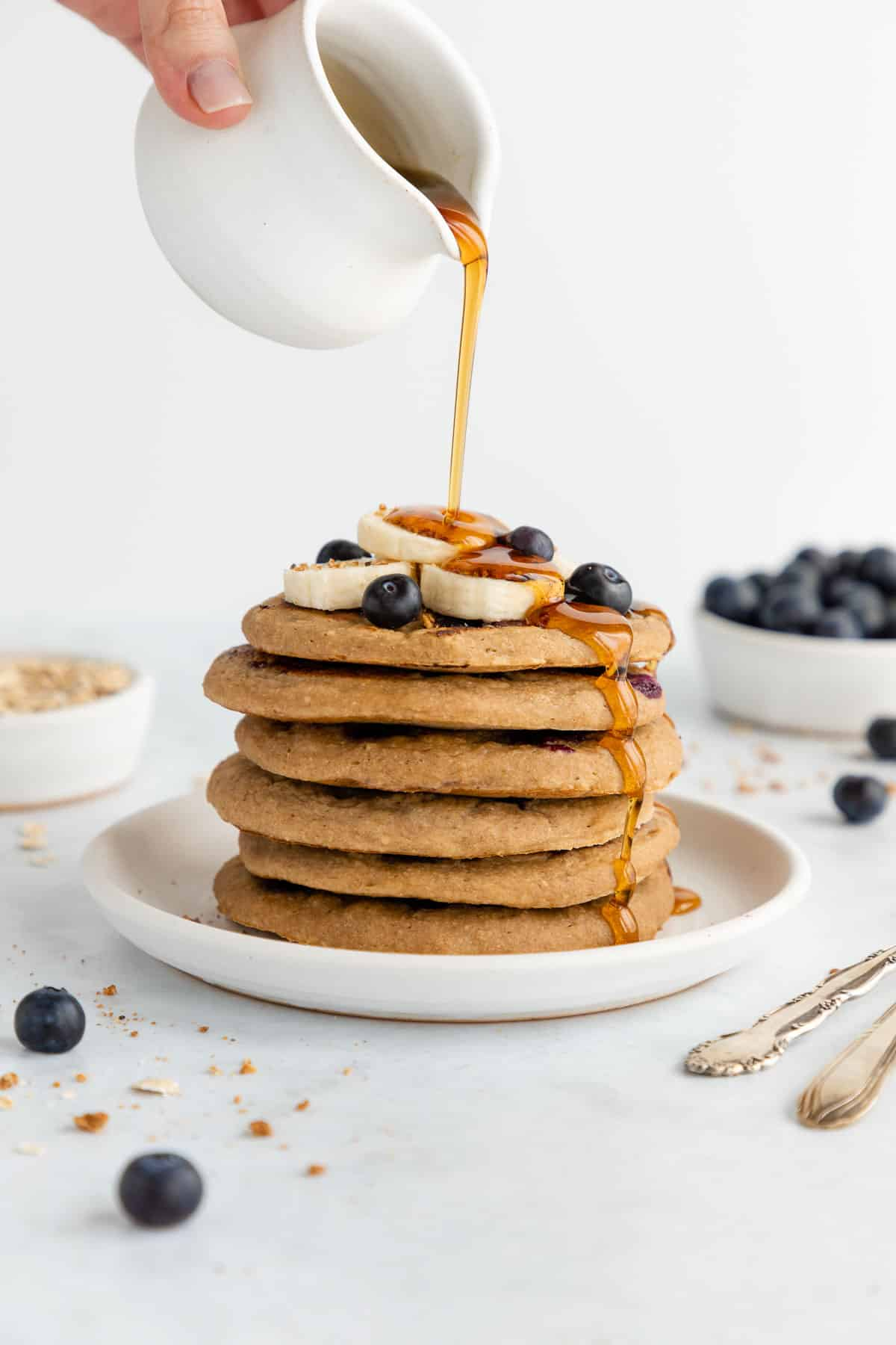 a hand pouring maple syrup over a stack of vegan blueberry banana pancakes