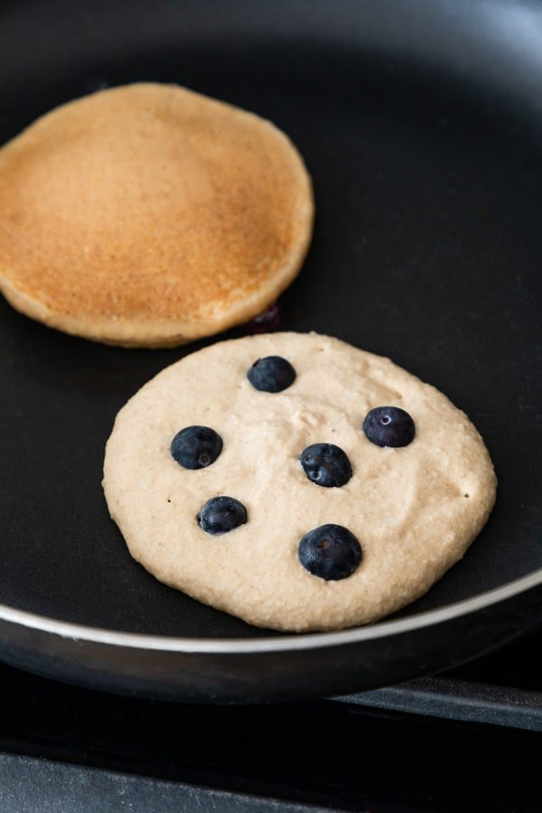two blueberry banana pancakes frying on a skillet