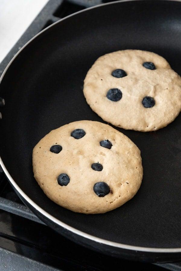 two vegan blueberry banana pancakes frying on a skillet