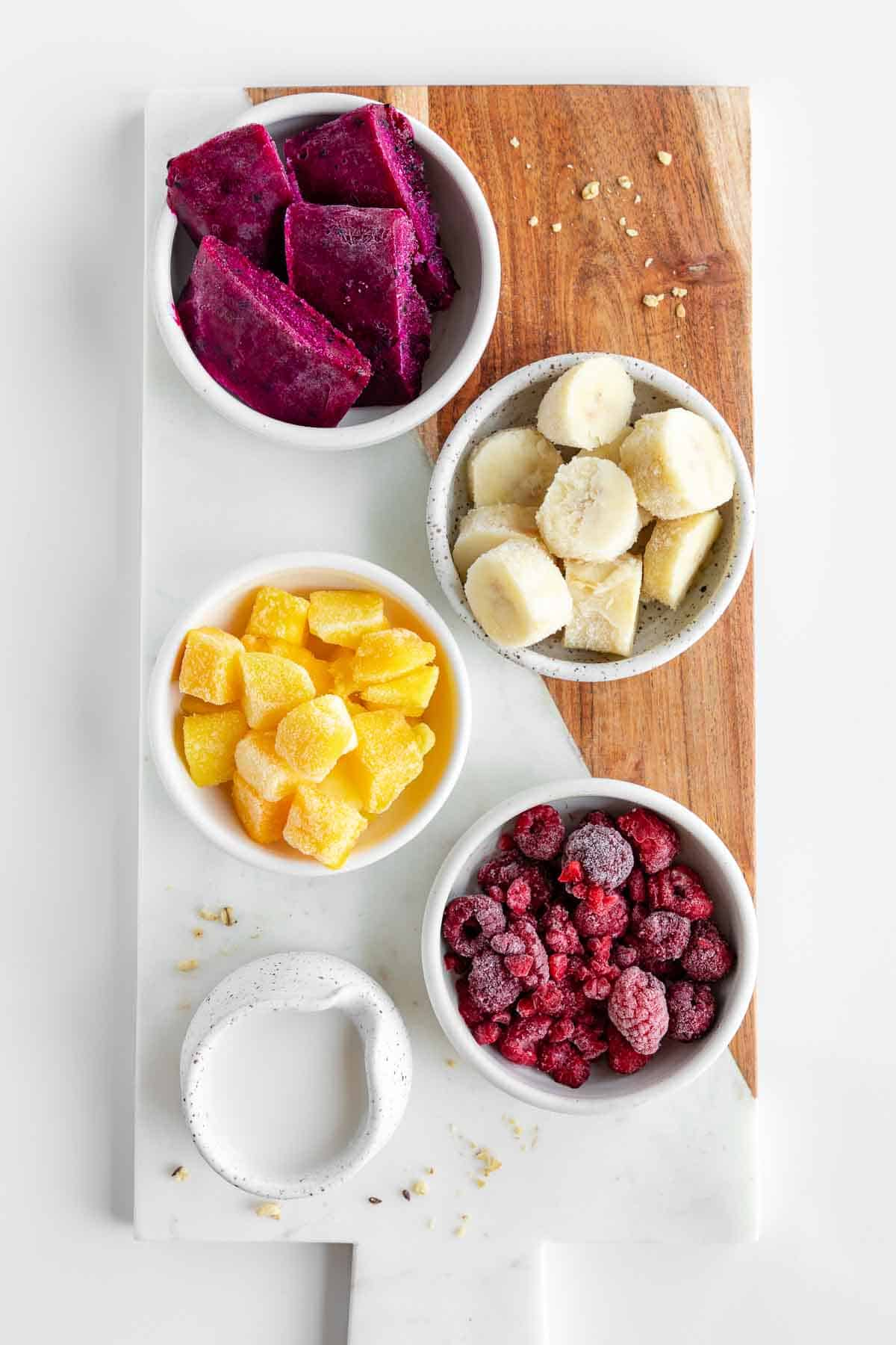 marble serving board topped with bowls of dragon fruit, frozen bananas, frozen mango chunks, frozen raspberries, and coconut milk