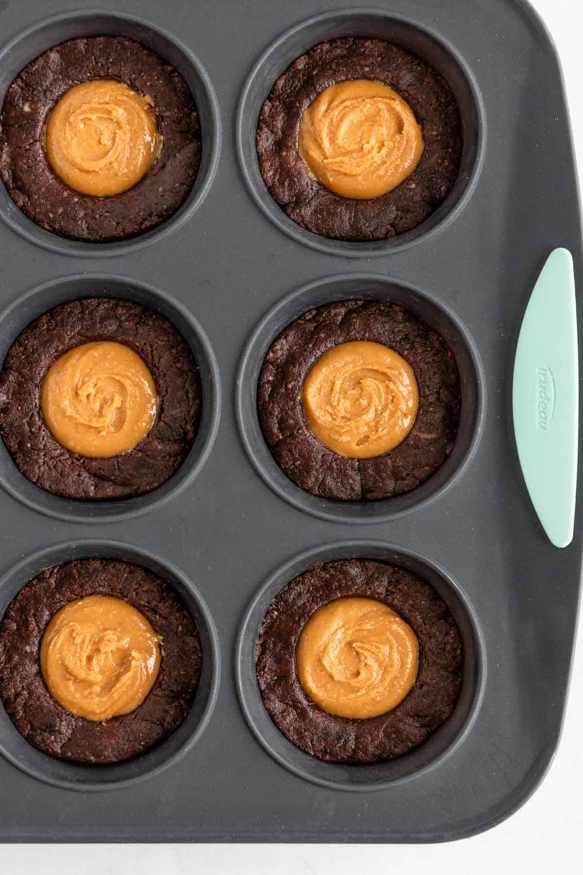 peanut butter brownie cups inside a silicone muffin tin