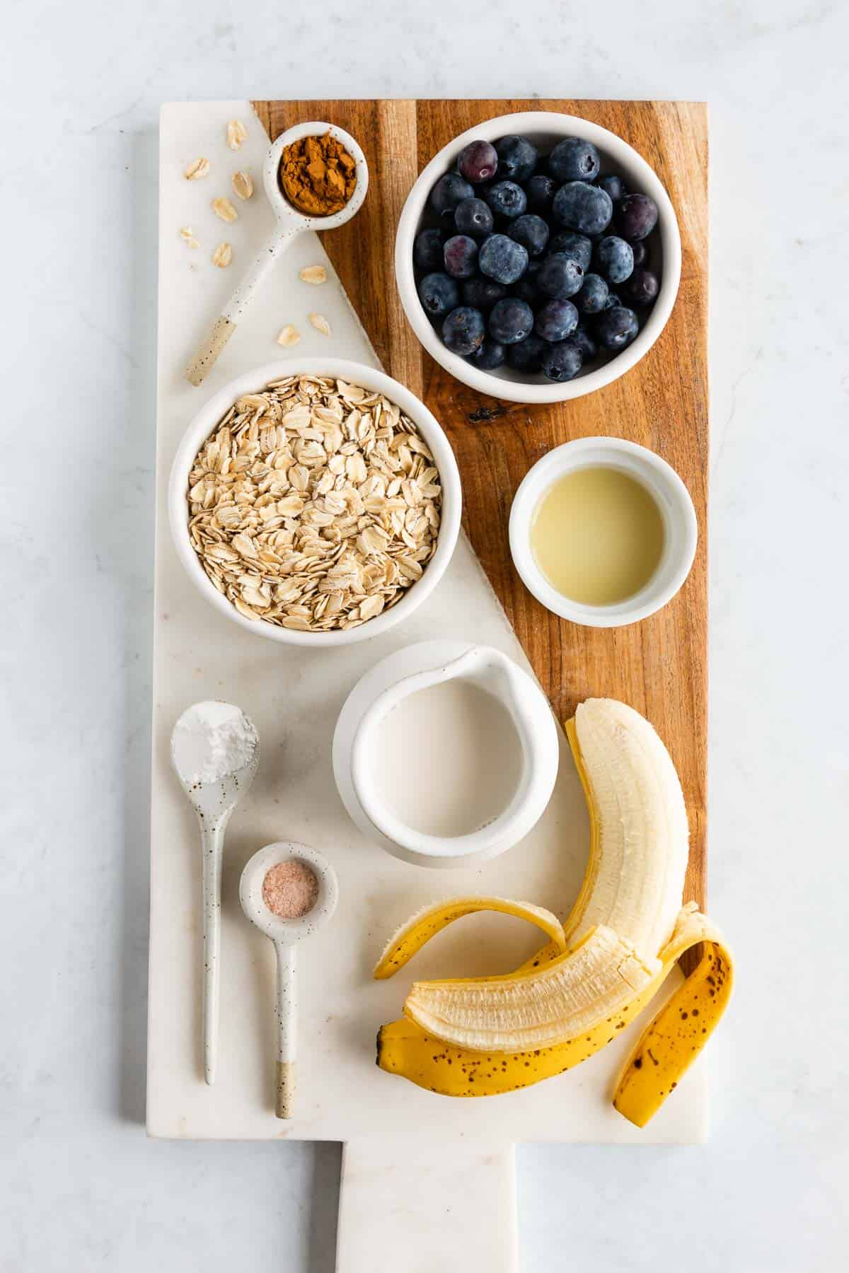 a marble and wood serving board topped with a peeled banana, rolled oats, blueberries, almond milk, cinnamon, baking powder, salt, and lemon juice