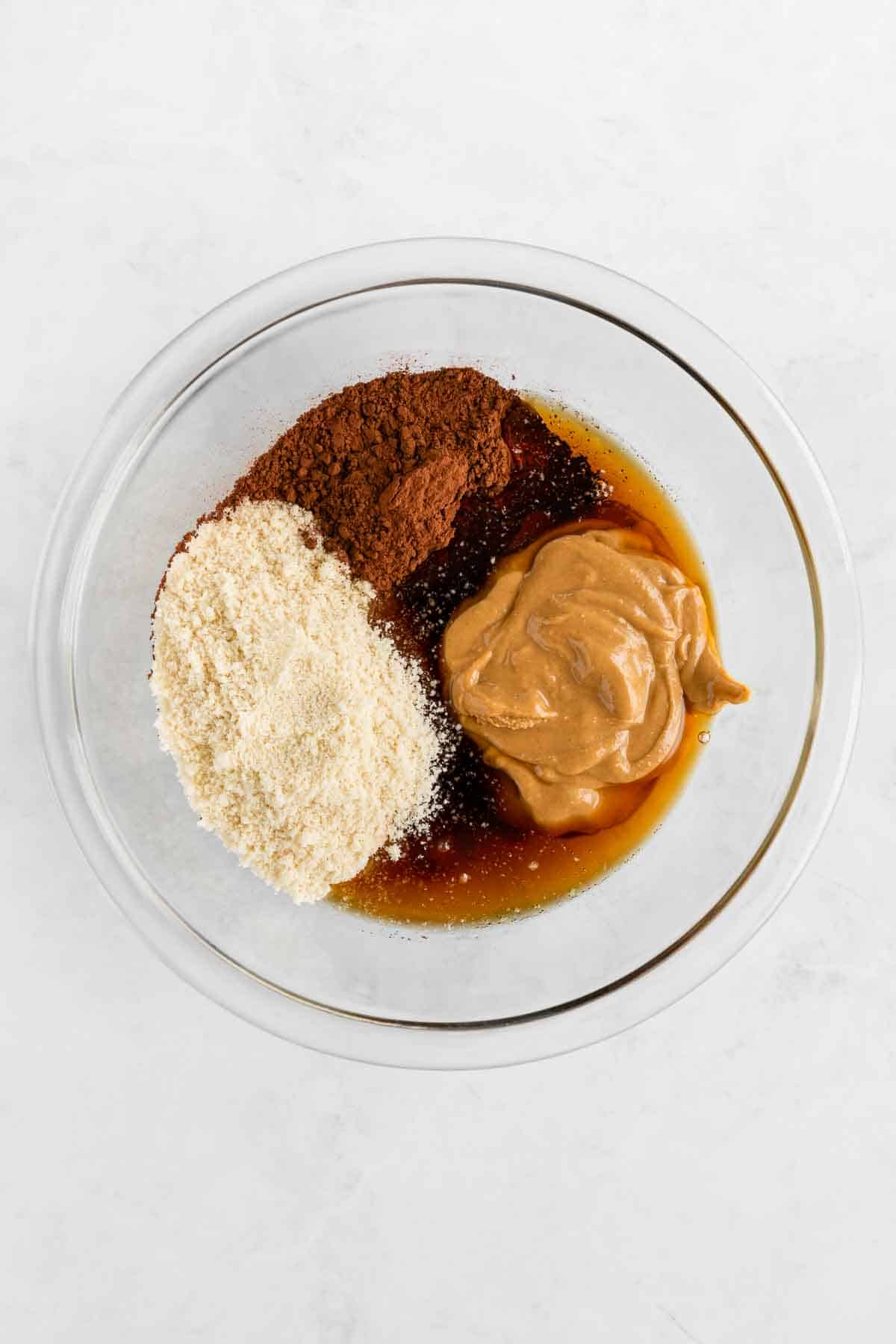 almond flour, peanut butter, cocoa powder, and maple syrup in a glass pyrex mixing bowl