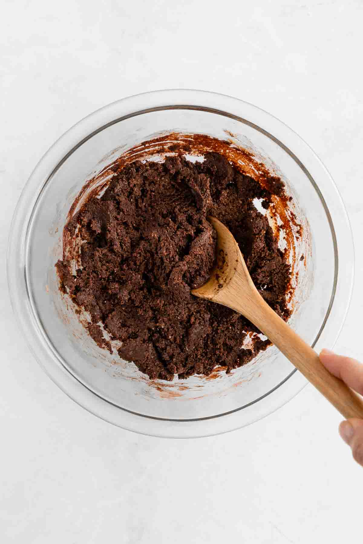 a wooden spoon mixing no bake brownie dough inside a glass bowl