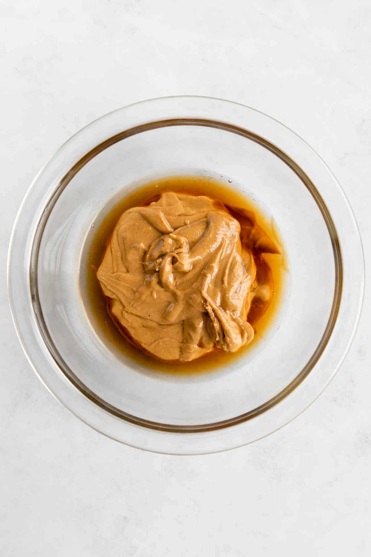 peanut butter and maple syrup in a glass pyrex mixing bowl