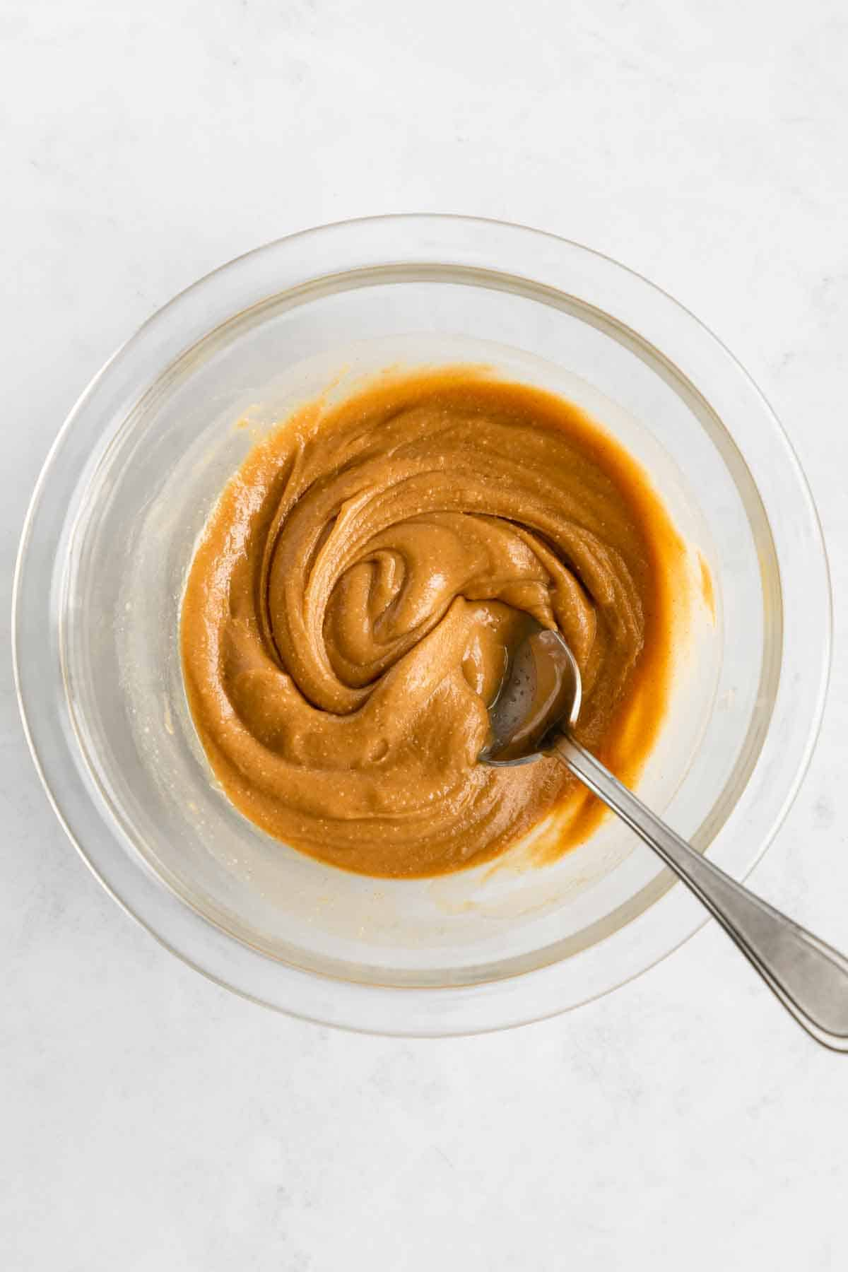 a spoon mixing peanut butter and maple syrup in a glass mixing bowl