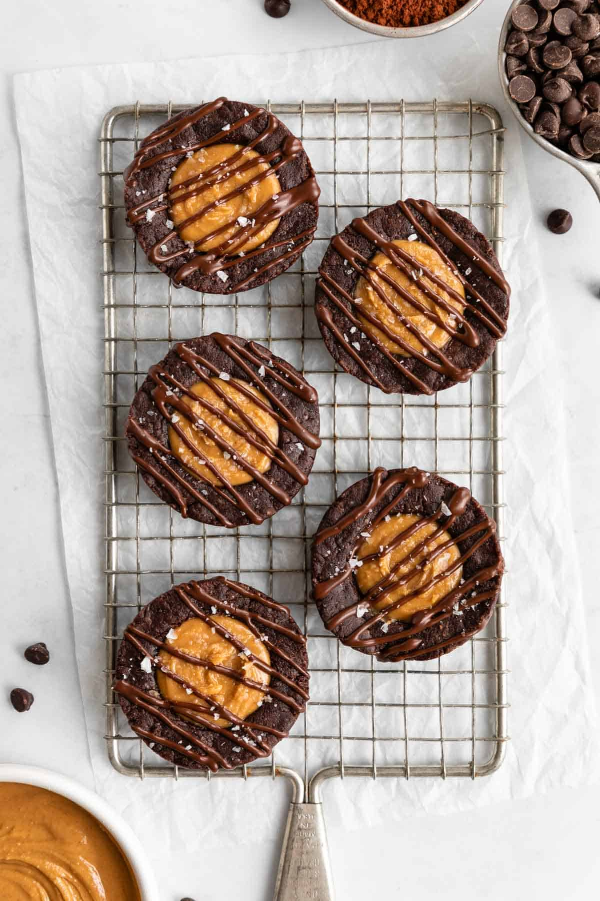 five no bake peanut butter brownie cups on a wire cooling rack beside a bowl of peanut butter