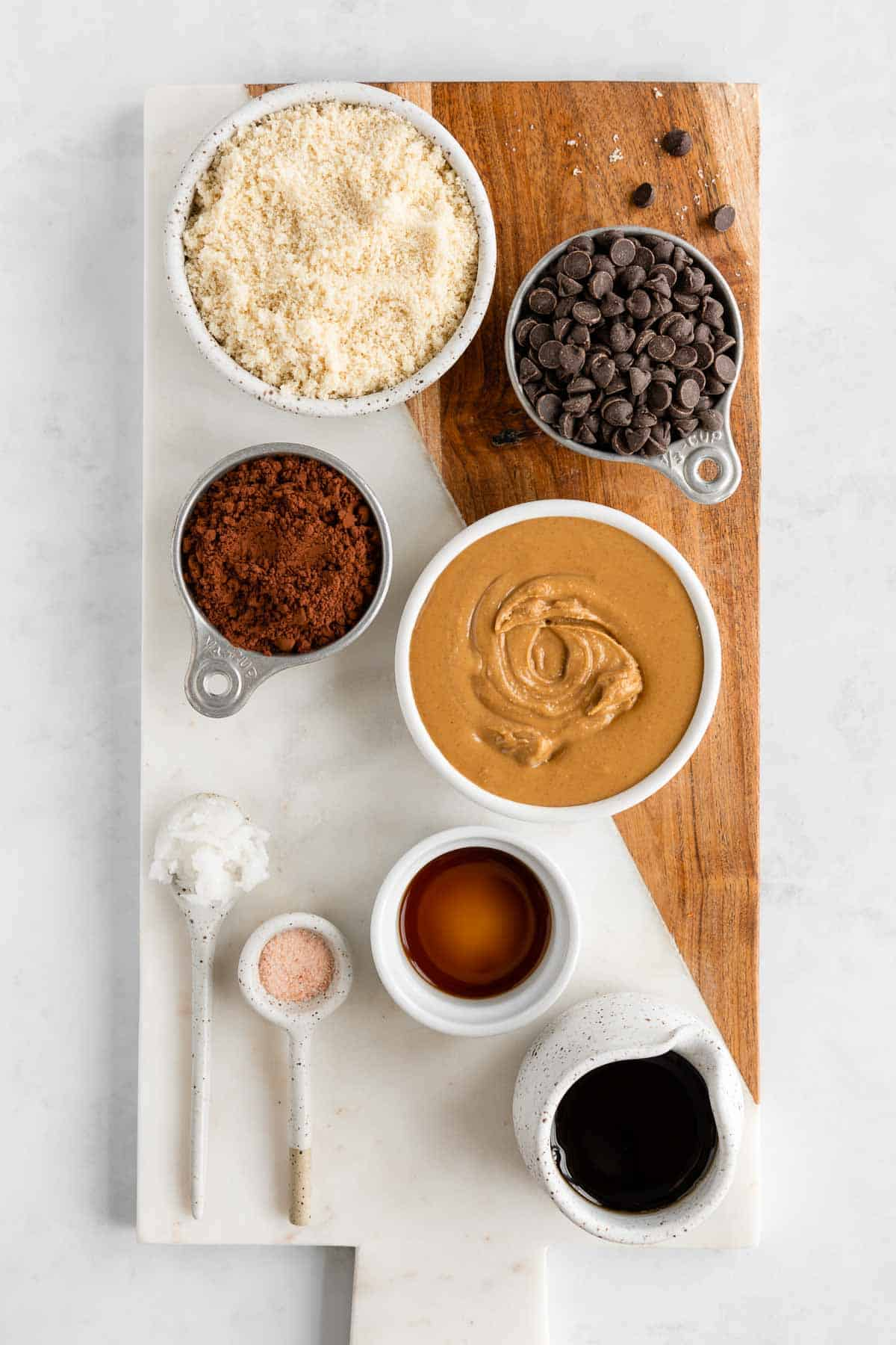 a marble serving board topped with bowls of almond flour, peanut butter, cocoa powder, maple syrup, chocolate chips, and vanilla extract