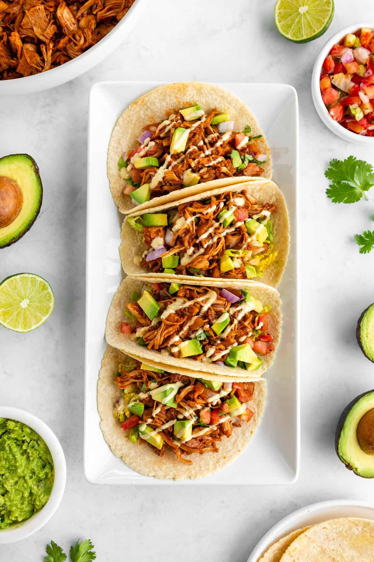 four vegan jackfruit tacos on a white rectangular plate surrounded by ingredients