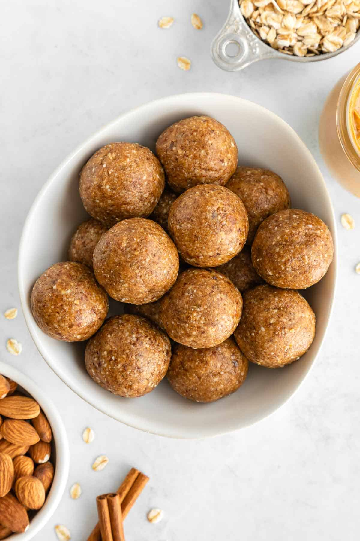 a bowl of almond butter energy balls beside almonds, rolled oats, and cinnamon sticks