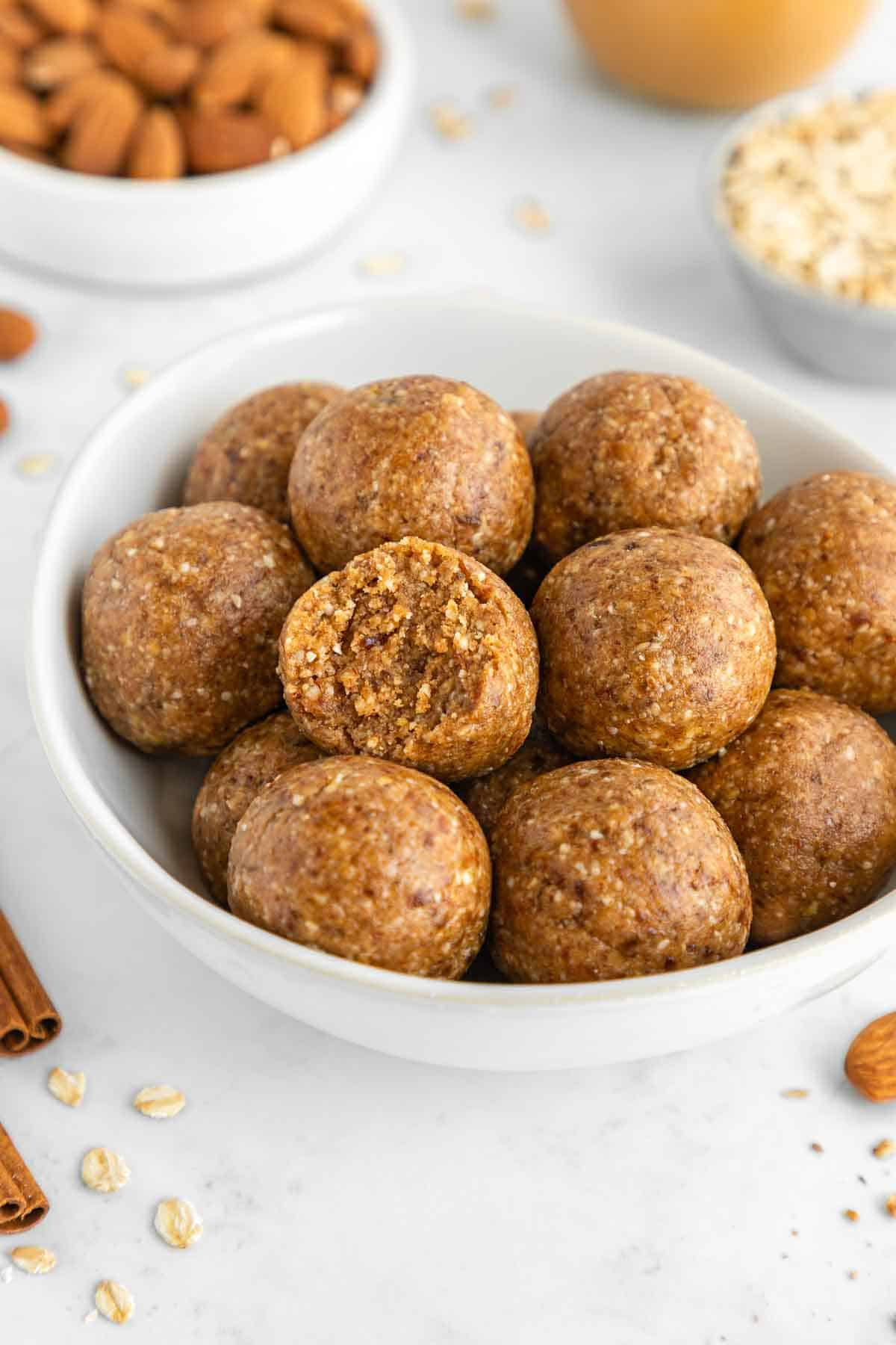 a white bowl filled with almond butter energy balls and a bite taken out of the middle one