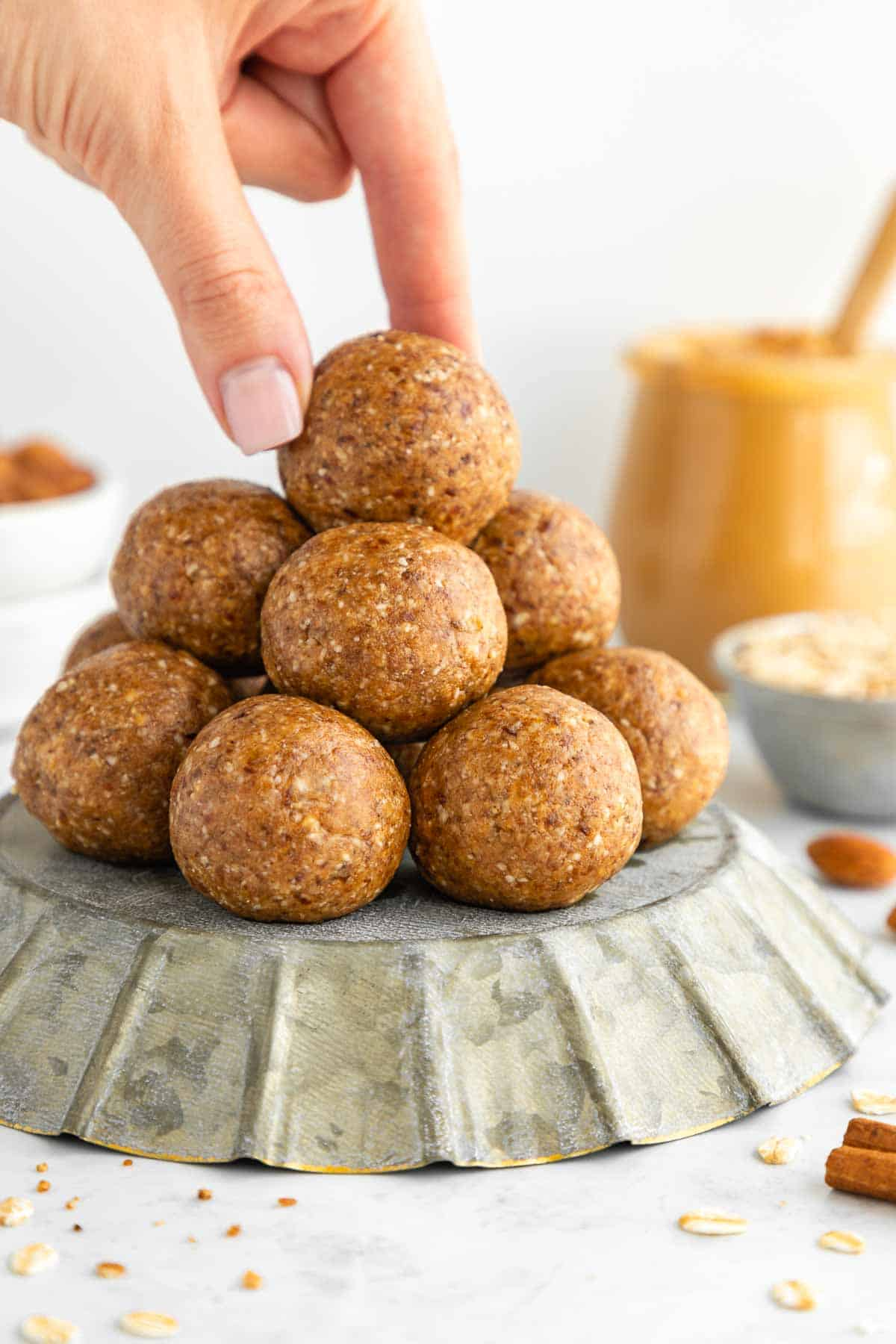 a hand grabbing a stack of almond butter energy balls on a pie pan