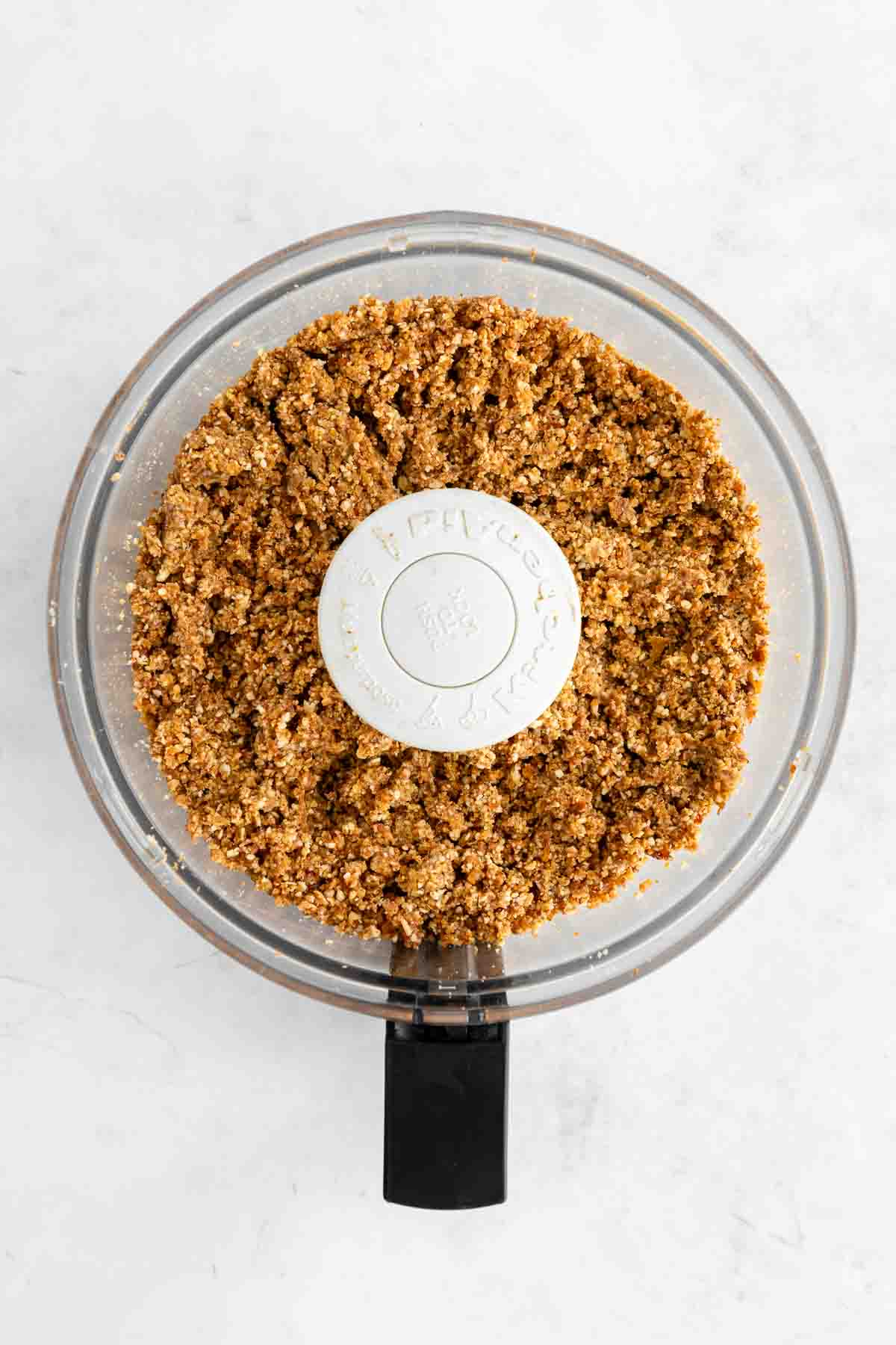 a mixture of dates, nuts, and oats blended inside a food processor