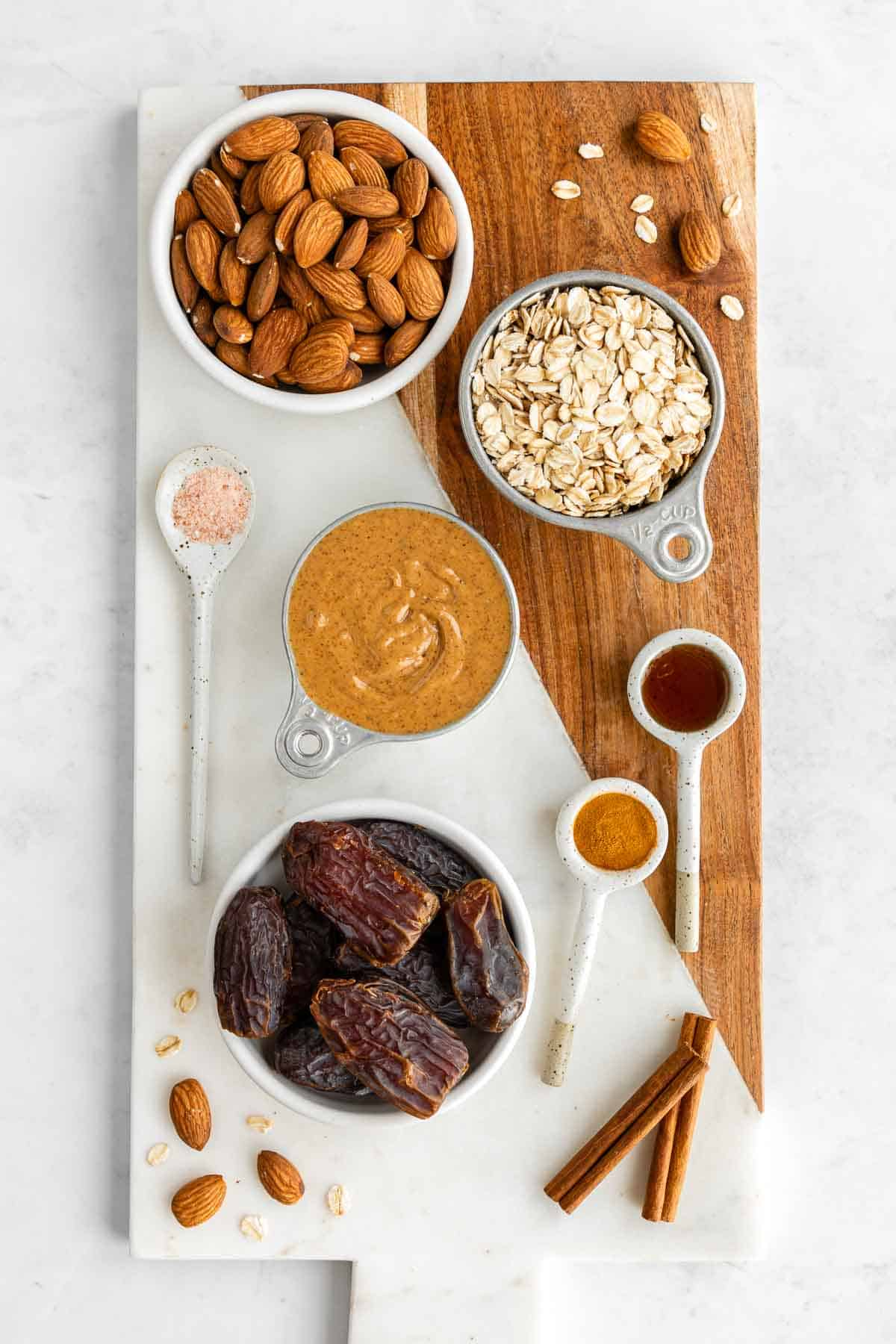 a marble and wood board topped with bowls of almonds, oats, dates, vanilla, cinnamon, and salt